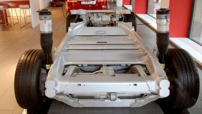 A vehicle's chassis frame and a Tesla Model S 100D car stand in a showroom of U.S. car manufacturer Tesla in Zurich, Switzerland March 28, 2018. REUTERS/Arnd Wiegmann - RC1EDDA7BA30