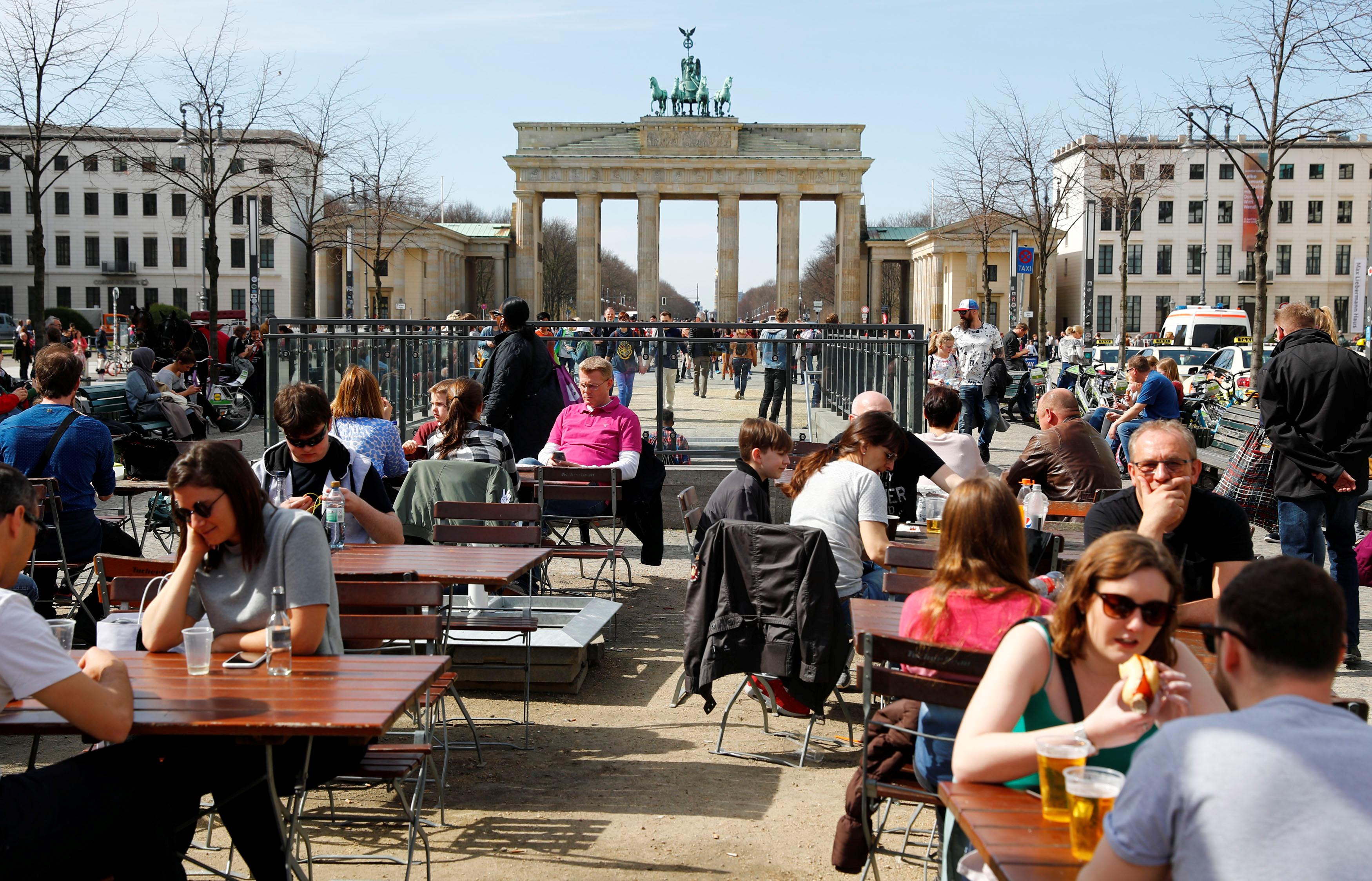 People enjoy sunny weather at the Brandenburg Gate in Berlin