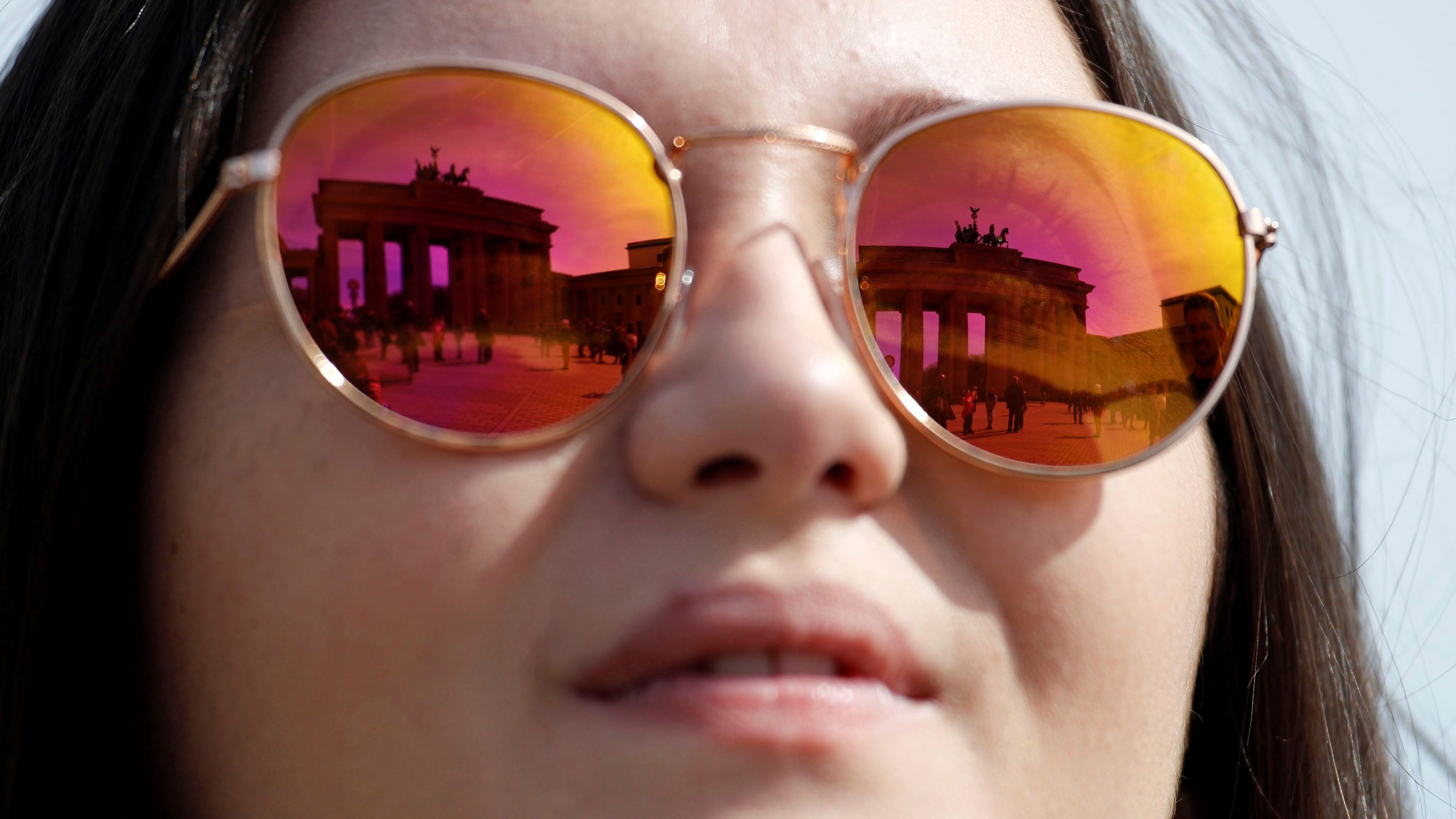 A British tourist poses for the photographer as the Brandenburg Gate is reflected in her sunglasses, in Berlin