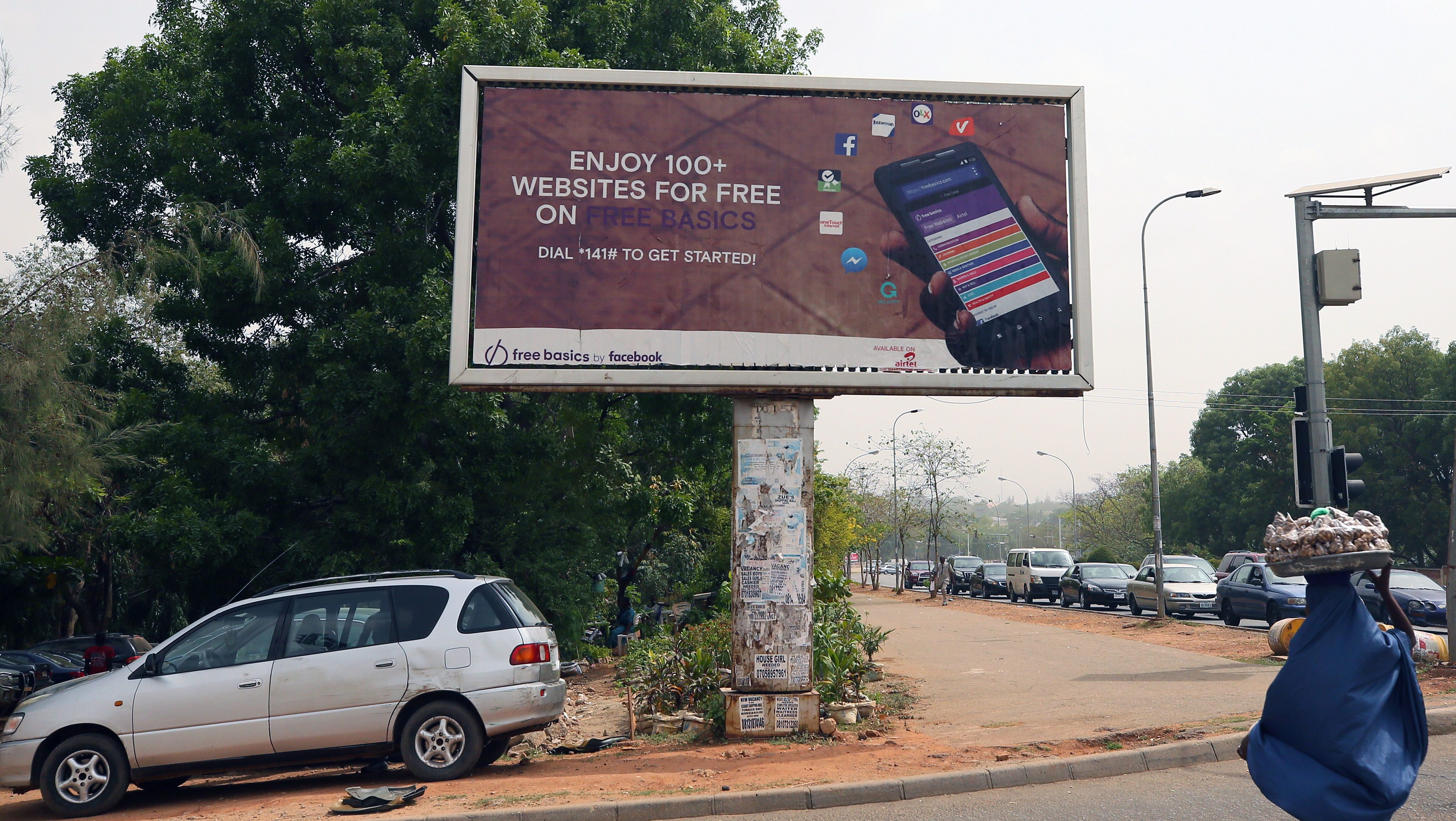 A woman walks past an advertising billboard for Free Basics, a service from Facebook, along a street in Abuja, Nigeria April 4, 2018.