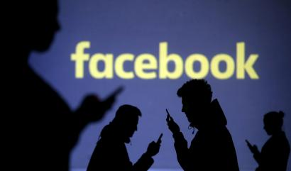 FILE PHOTO: Silhouettes of mobile users are seen next to a screen projection of Facebook logo in this picture illustration taken March 28, 2018.