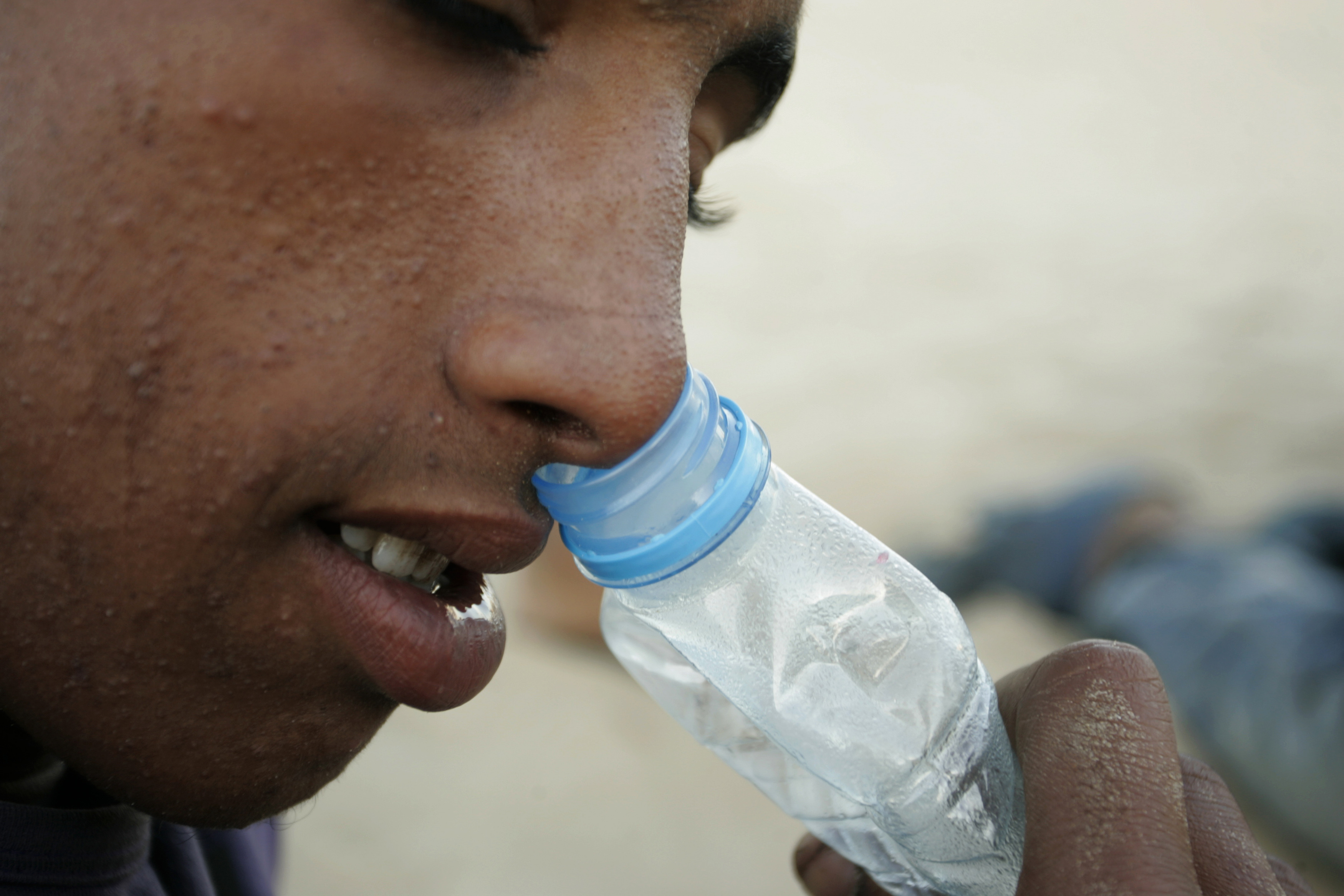 A homeless boy sniffs glue at a beach in Tangier October 9, 2009. More than 10000 homeless minors live on the streets of Morocco according to the Al Jaima association, an association that works with street kids, most of them being victims of drugs and prostitution. REUTERS/Rafael Marchante (MOROCCO SOCIETY) - GM1E5AA0FNK01