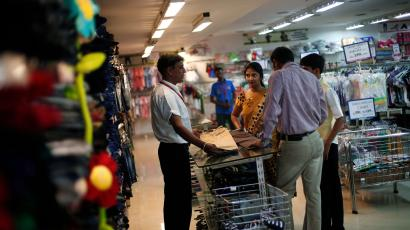 Sales assistant shows clothing to customers inside a V-Mart retail store in New Delhi