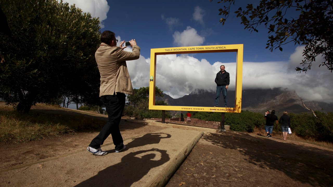 Visitors pose for pictures against Table Mountain at a viewing site in Cape Town, South Africa, April 29, 2015. South Africa's tourism industry is likely to take a hit following a wave of xenophobic attacks this month, a setback for the country which has worked hard to clean up its image as a hub for violent crime. April 29, 2015.  REUTERS/Mike Hutchings - GF10000077528