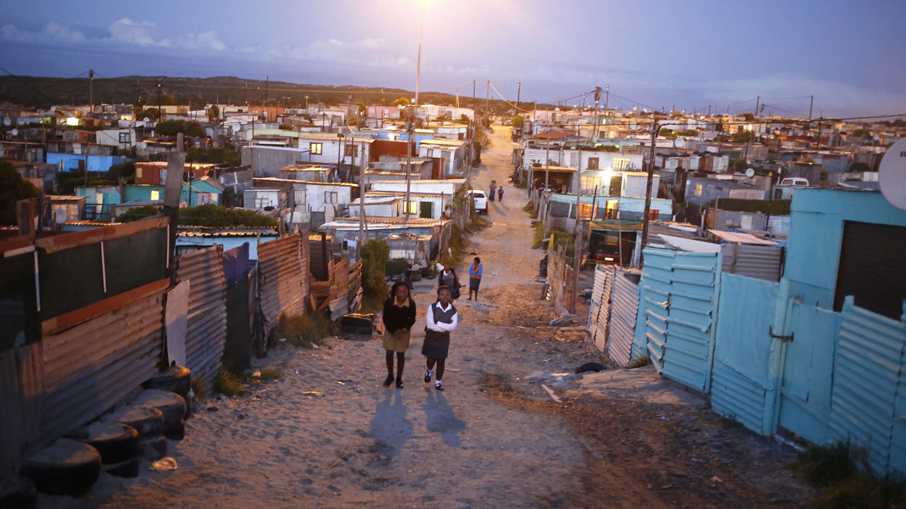 """In this photo taken on Tuesday, April 22, 2014, Liyabola Ndyumbu, aged twelve, center right, and her friend Aphiwe Stokwe, aged eleven, walk to their school in Khyalitsha township on the outskirts of Cape Town, South Africa. As South Africa marks the 20th anniversary of multiracial democracy on Sunday, April 27 the achievements and soaring expectations of what was dubbed a """"rainbow nation"""" have been tempered by a different inequality - the yawning gulf between rich and poor. (AP Photo/Schalk van Zuydam)"""