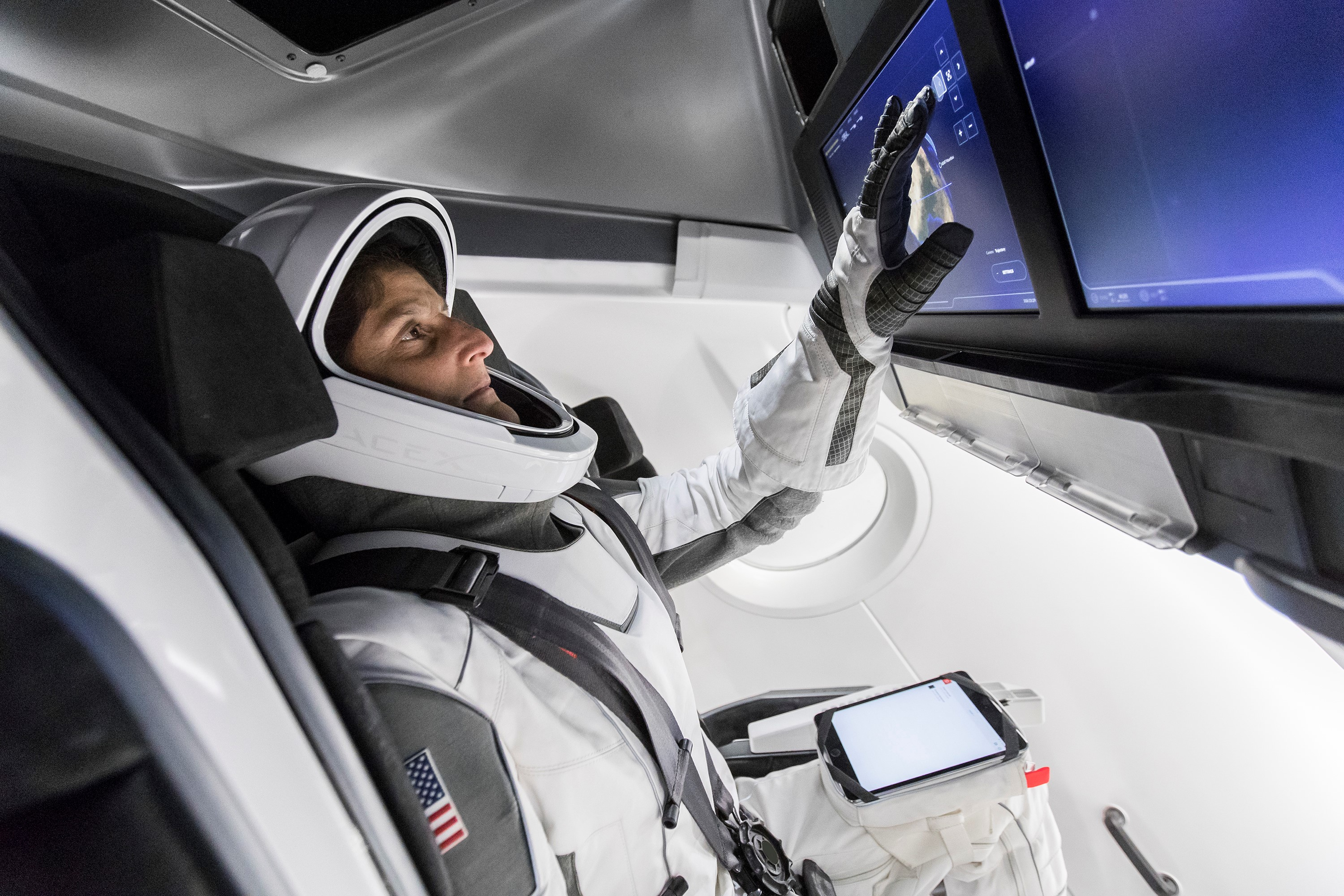 """""""NASA astronaut Suni Williams, fully suited in SpaceX's spacesuit, interfaces with the display inside a mock-up of the Crew Dragon spacecraft."""""""