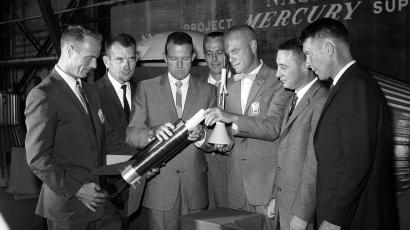 Seven astronauts training for rocket travel into space-and safe return to earth-look over a model of a test rocket at Langley Research Center, Va., on July 7, 1959. From Left to right are Navy Lt. Malcolm Carpenter, Air Force Capt. Donald Slayton, Air Force Capt. Leroy Cooper, Navy Lt. Cmdr. Alan Shepard, Marine Lt. Col. John Glenn, Air Force Capt. Virgil Guiesom and Navy Lt. Cmdr. Walter Schirra.