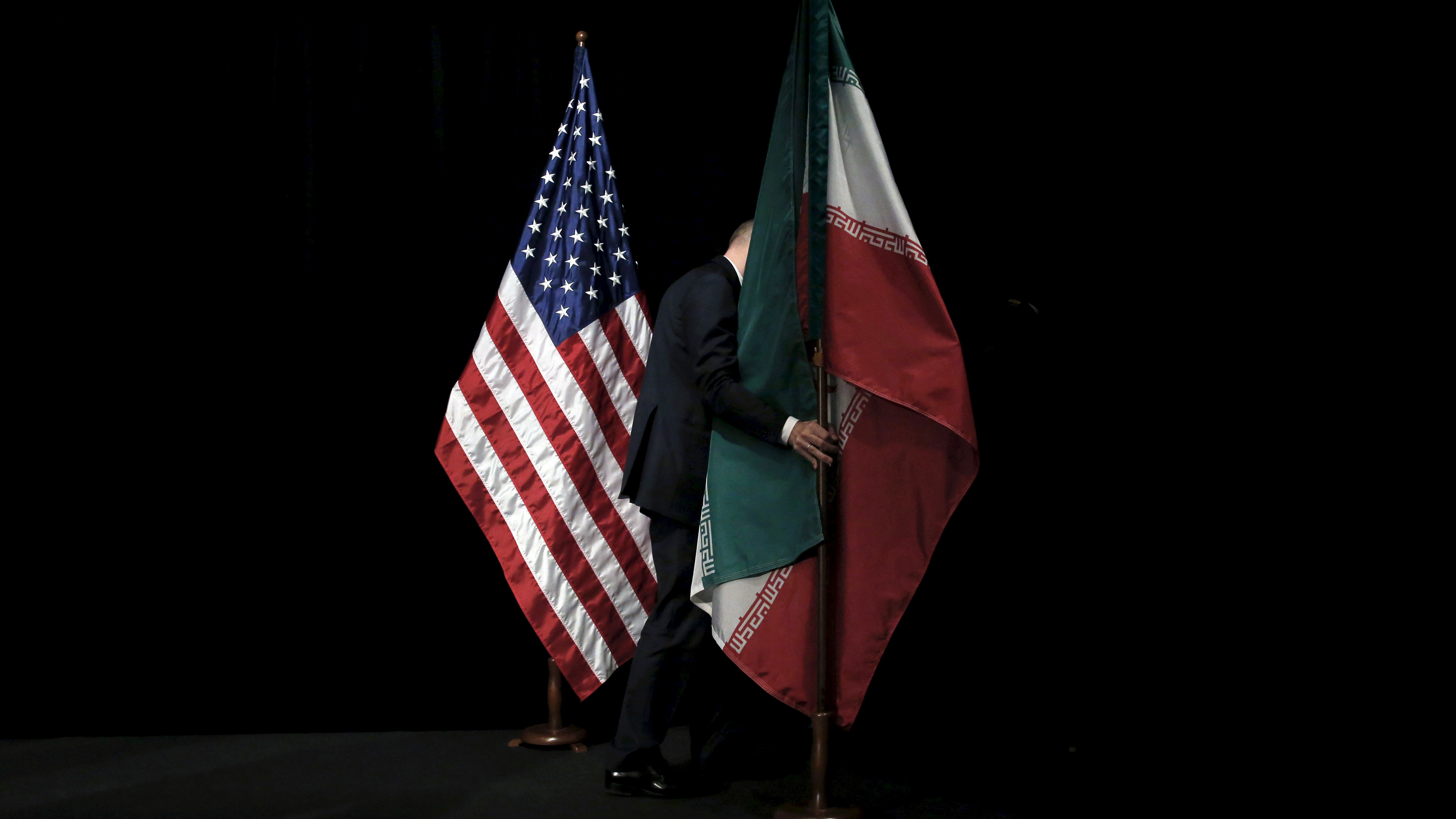 "A staff member removes the Iranian flag from the stage after a group picture with foreign ministers and representatives of Unites States, Iran, China, Russia, Britain, Germany, France and the European Union during the Iran nuclear talks at the Vienna International Center in Vienna, Austria July 14, 2015. Iran and six major world powers reached a nuclear deal on Tuesday, capping more than a decade of on-off negotiations with an agreement that could potentially transform the Middle East, and which Israel called an ""historic surrender"".  REUTERS/Carlos Barria       TPX IMAGES OF THE DAY - GF10000158897"