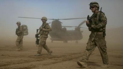 US soldiers walking in front of a helicopter.