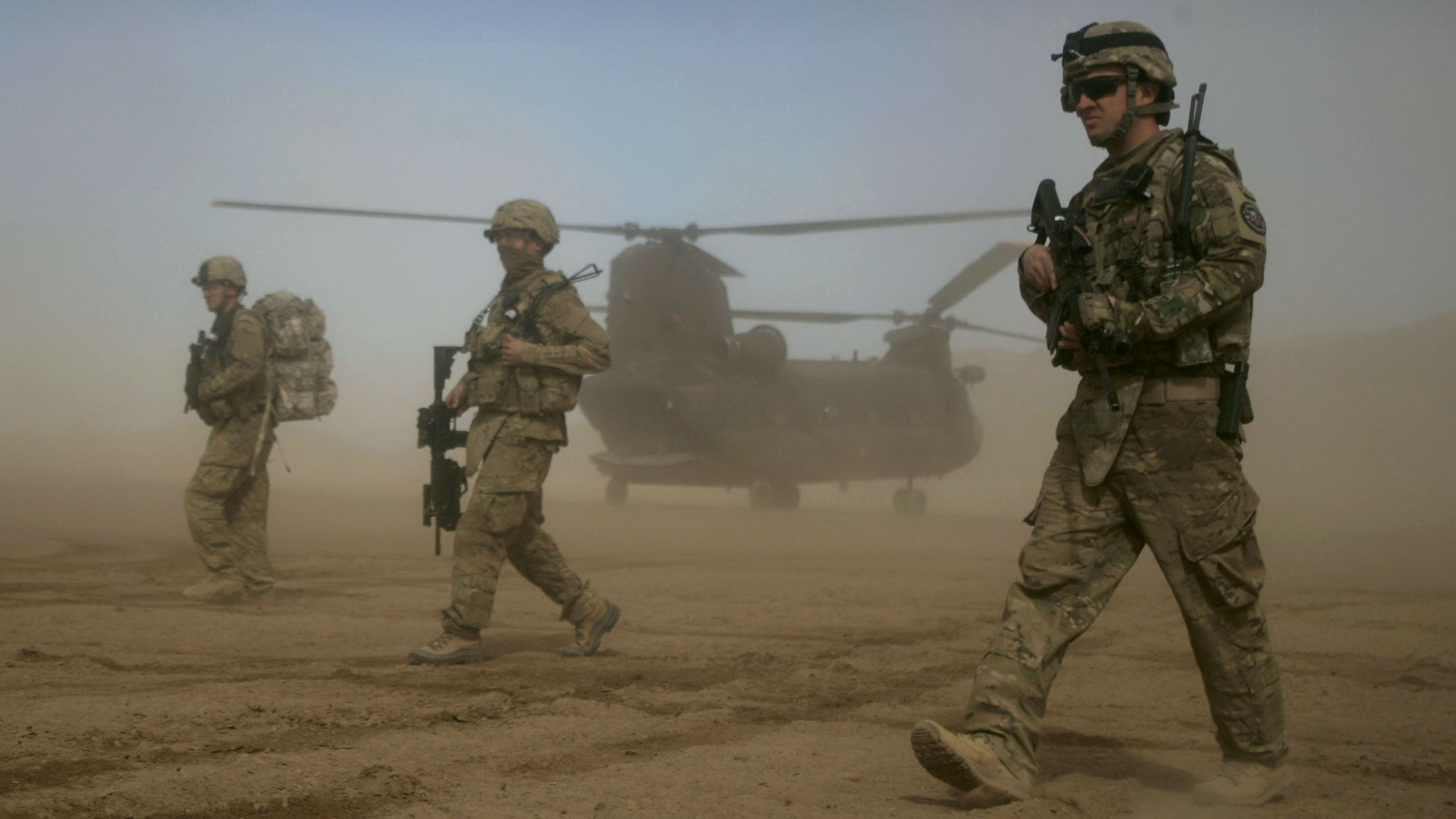 U.S. soldiers part of the NATO- led International Security Assistance Force (ISAF) walks, as a U.S. Chinook helicopter is seen on the back ground near the place where the foundation of a hospital was laid in Shindand, Herat, west of Kabul, Afghanistan, Saturday, Jan. 28, 2012. The foundation of a U.S. military funded 50 beds hospital was laid with the cost of 400, 000 US dollar in Shindand of Herat, the hospital project is expected to be completed in 18 months.