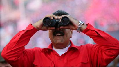 Venezuela's President Nicolas Maduro uses binoculars during a campaign rally in Cumana, Venezuela May 11, 2018.