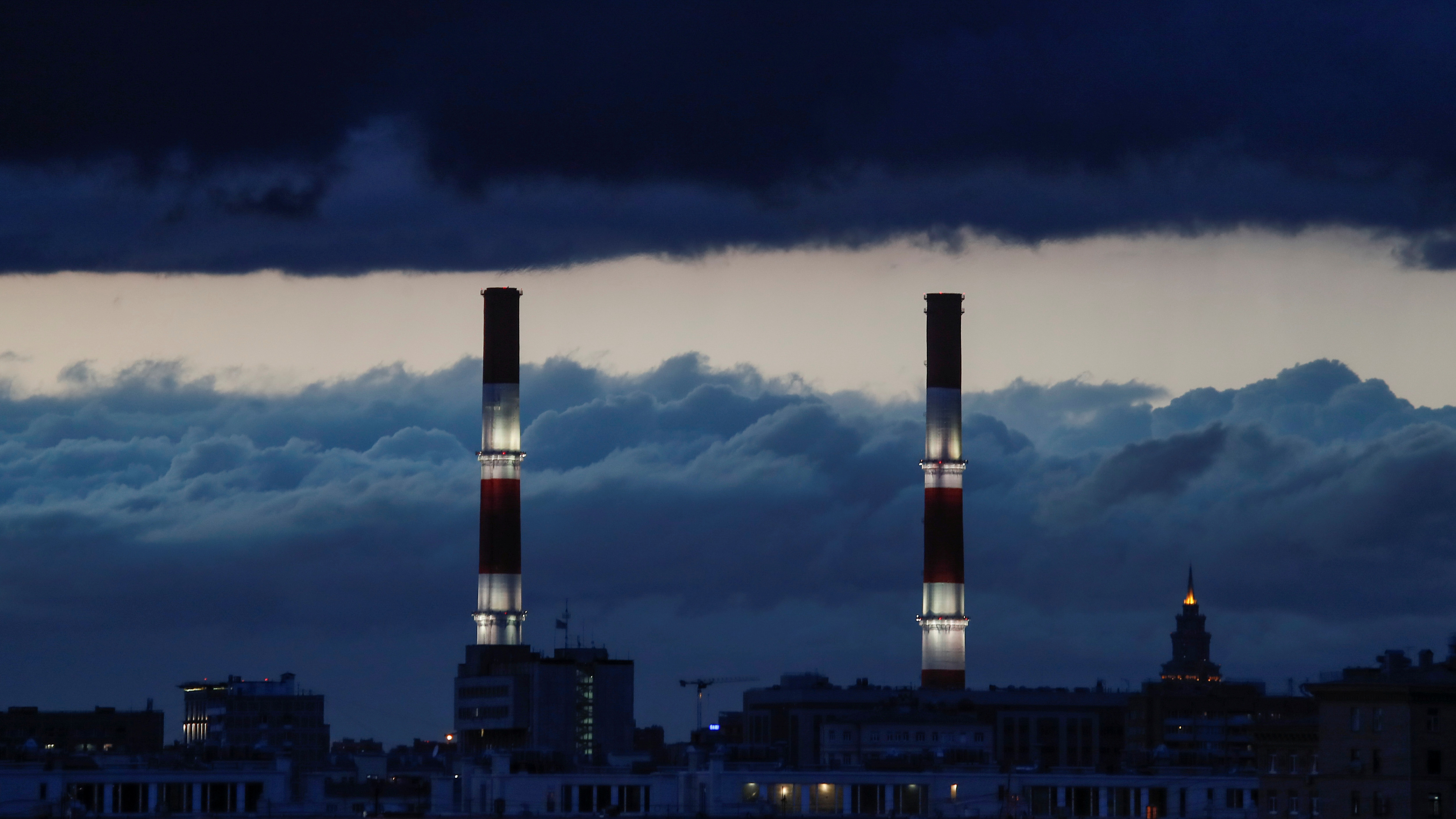 Chimneys of a heating power plant are pictured on a stormy evening in Moscow, Russia, April 21, 2018.  REUTERS/Maxim Shemetov - RC1BEC042D40