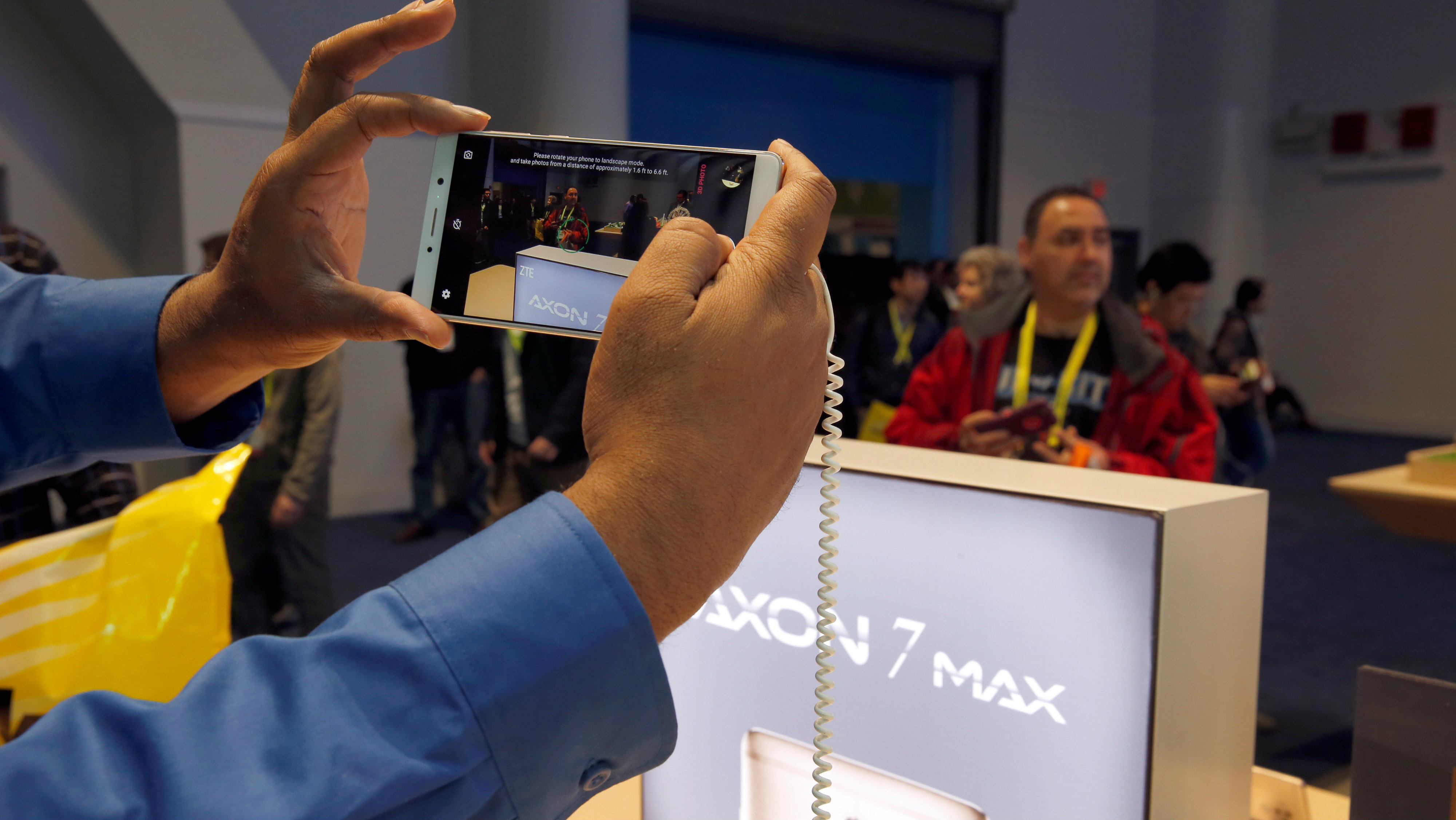 A man takes a photo with an Axon 7 Max smartphone with 3D camera at the ZTE booth during the 2017 CES in Las Vegas, Nevada January 6, 2017