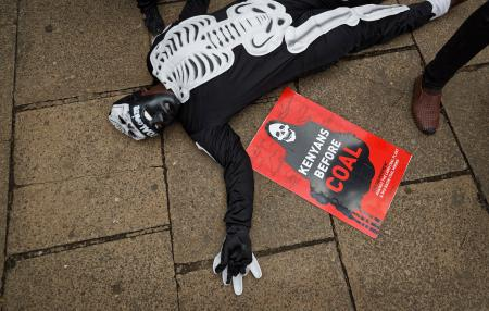 An environmental protester lies on the ground as he demonstrates against recent government plans to mine coal and open a coal-fired power plant, in downtown Nairobi, Kenya Tuesday, June 5, 2018. Kenyan activists protested plans for the joint venture between the Kenyan and Chinese governments in Lamu County, saying it will have devastating effect on the environment and health of local populations.