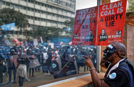 An environmental protester points his finger at the reflective window of the Ministry of Interior, as he demonstrates against recent government plans to mine coal and open a coal-fired power plant, in downtown Nairobi, Kenya Tuesday, June 5, 2018. Kenyan activists protested plans for the joint venture between the Kenyan and Chinese governments in Lamu County, saying it will have devastating effect on the environment and health of local populations.