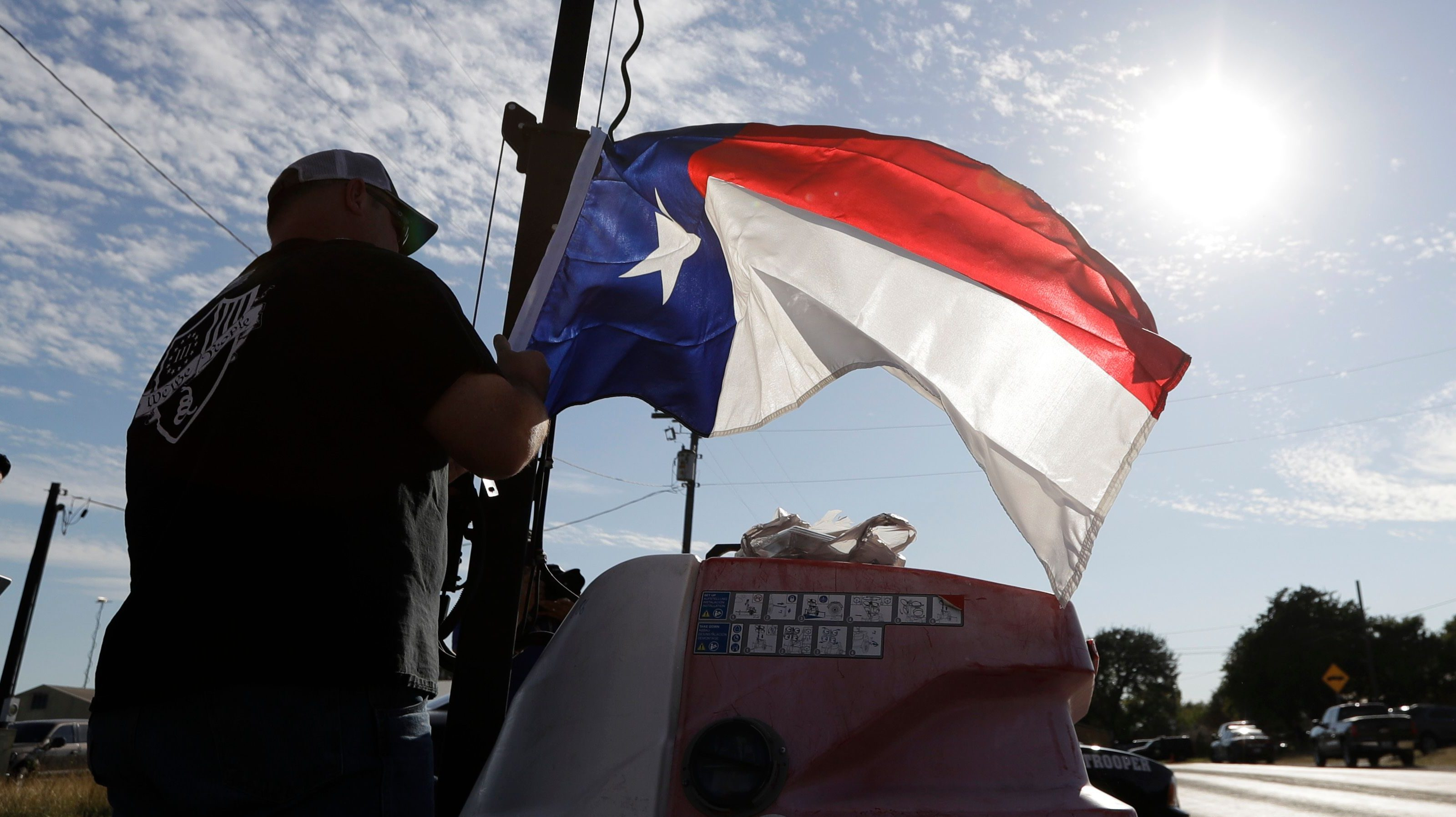 Jim Thompson places a Texas flag at a makeshift memorial near the scene of a shooting at the First Baptist Church of Sutherland Springs to honor victims on November 6, 2017, in Sutherland Springs, Texas.