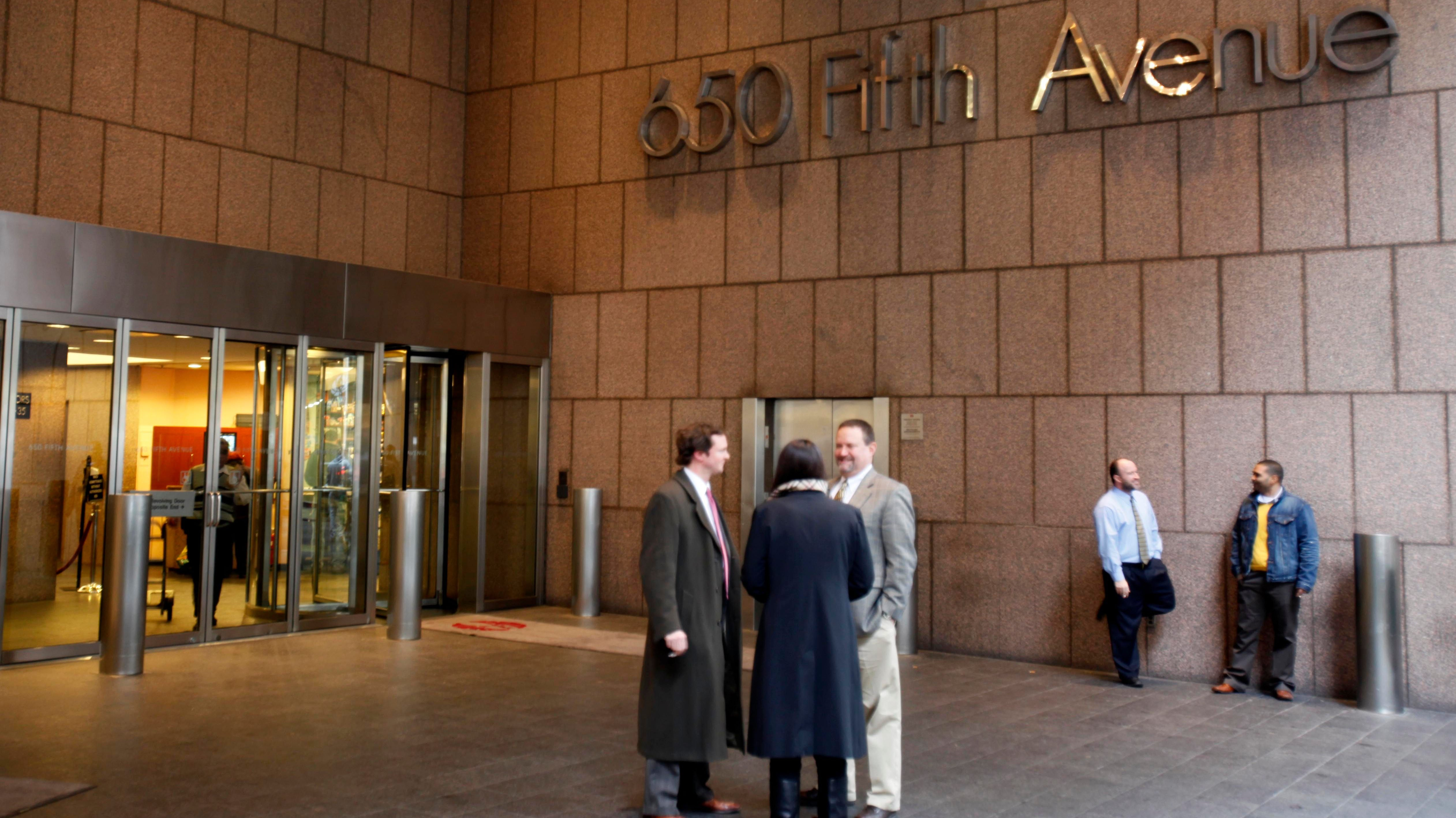 People stand near an entrance to 650 5th Ave in New York on Thursday, Nov. 12, 2009. Federal prosecutors Thursday took steps to seize four U.S. mosques and this Fifth Avenue skyscraper owned by a nonprofit Muslim organization long suspected of being under Iranian government control. (AP Photo/Seth Wenig)