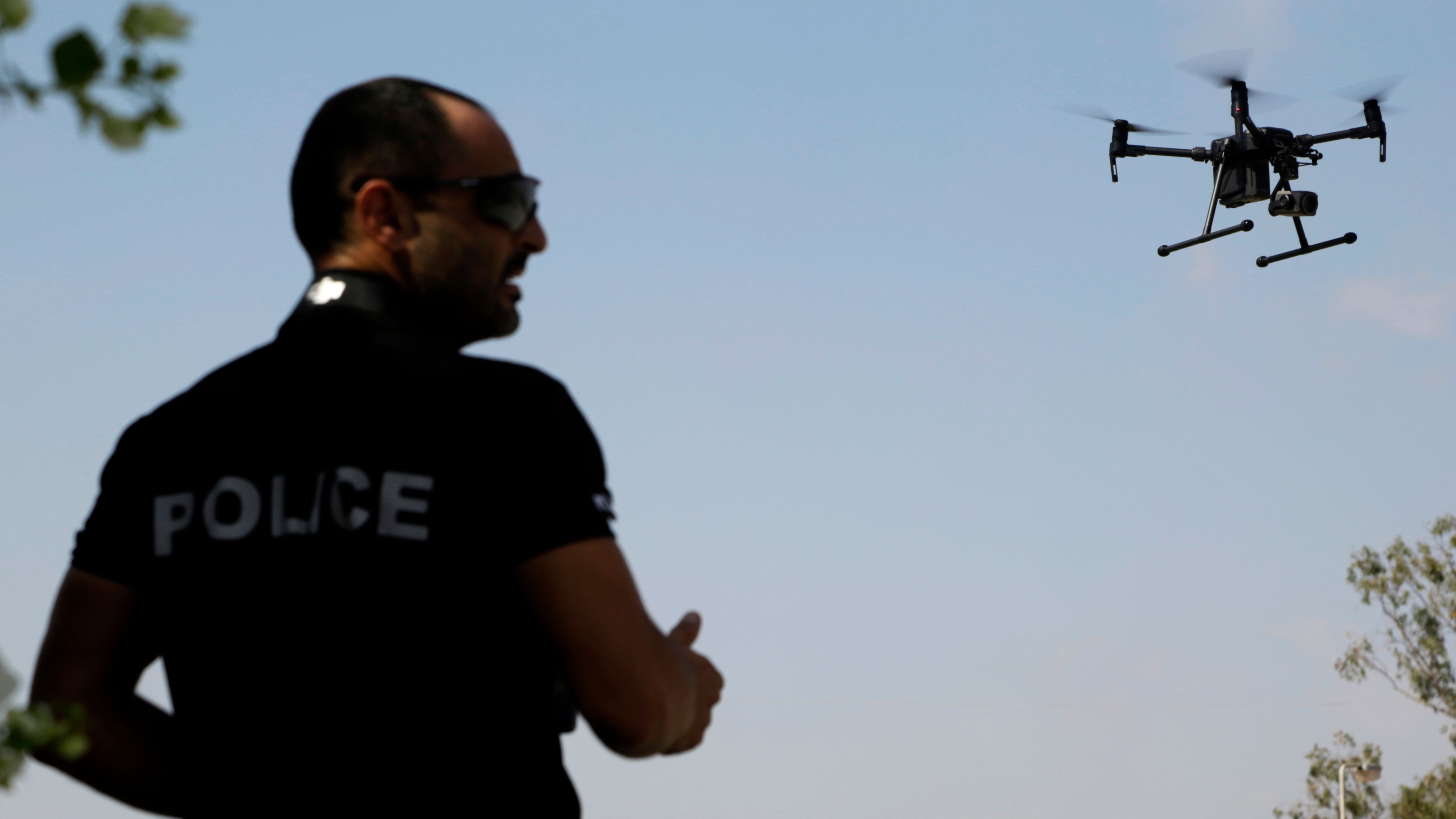 A police officer of SBA controls a drone during a demonstration at the British police station inside the British military base in Dhekelia in southeast of the island of Cyprus, Thursday, Sept. 21, 2017. Police at Britain's two military bases on Cyprus say the use of a state-of-the-art drone will greatly boost their ongoing crackdown on the illicit trapping of migratory birds. (AP Photo/Petros Karadjias)