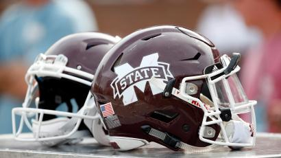Two football helmets from Mississippi State sitting on a chair.