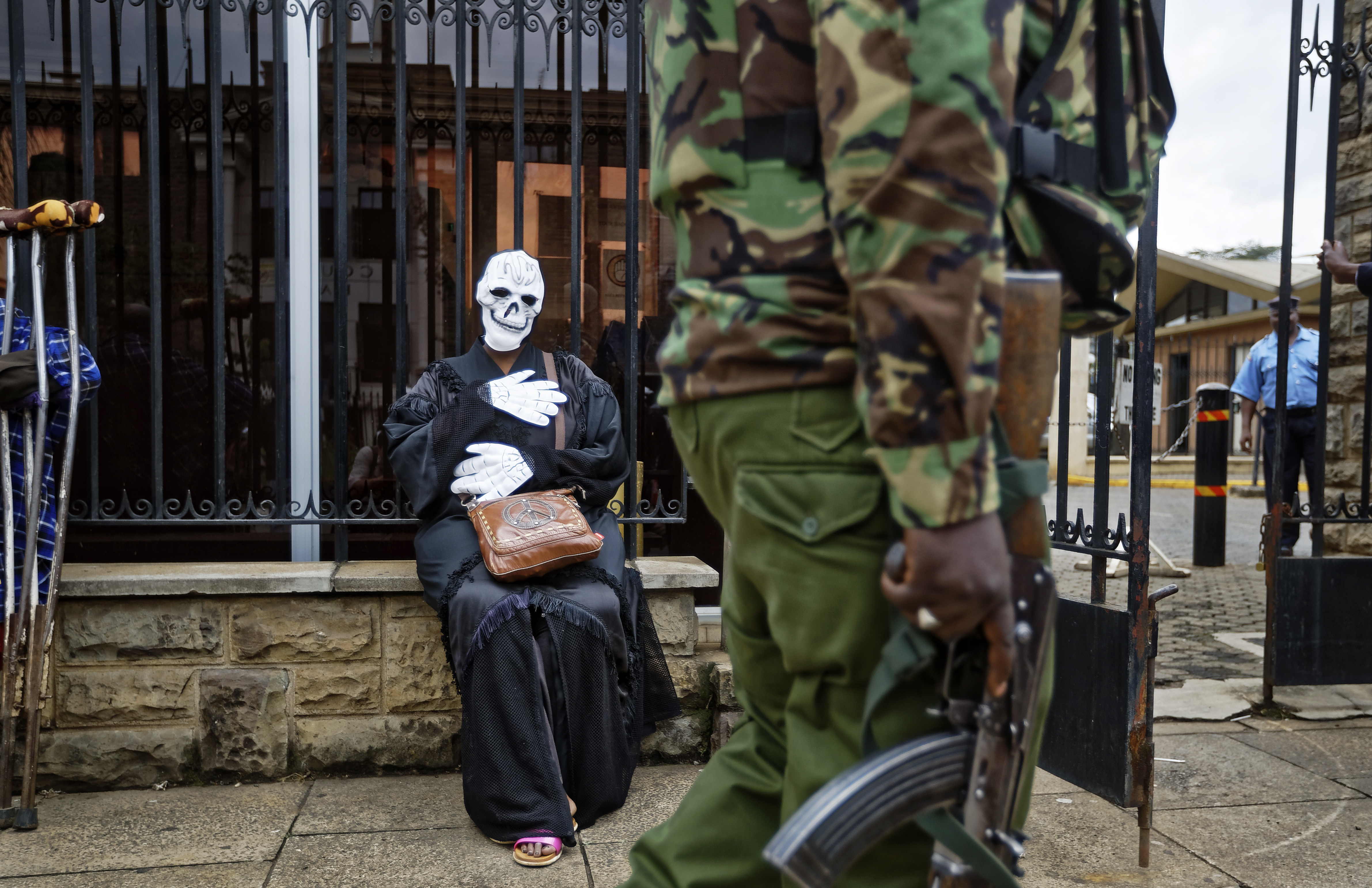 An armed police officer walks past an environmental protester wearing a skeleton costume as she demonstrates outside parliament against recent government plans to mine coal and open a coal-fired power plant, in downtown Nairobi, Kenya Tuesday, June 5, 2018. Kenyan activists protested plans for the joint venture between the Kenyan and Chinese governments in Lamu County, saying it will have devastating effect on the environment and health of local populations.