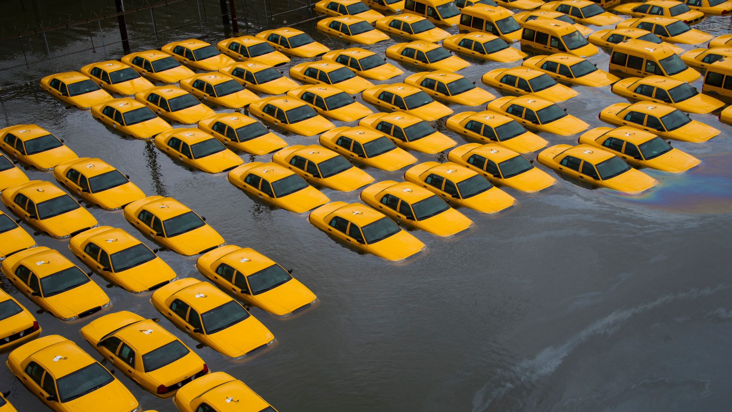 A flooded parking lot full of taxis.