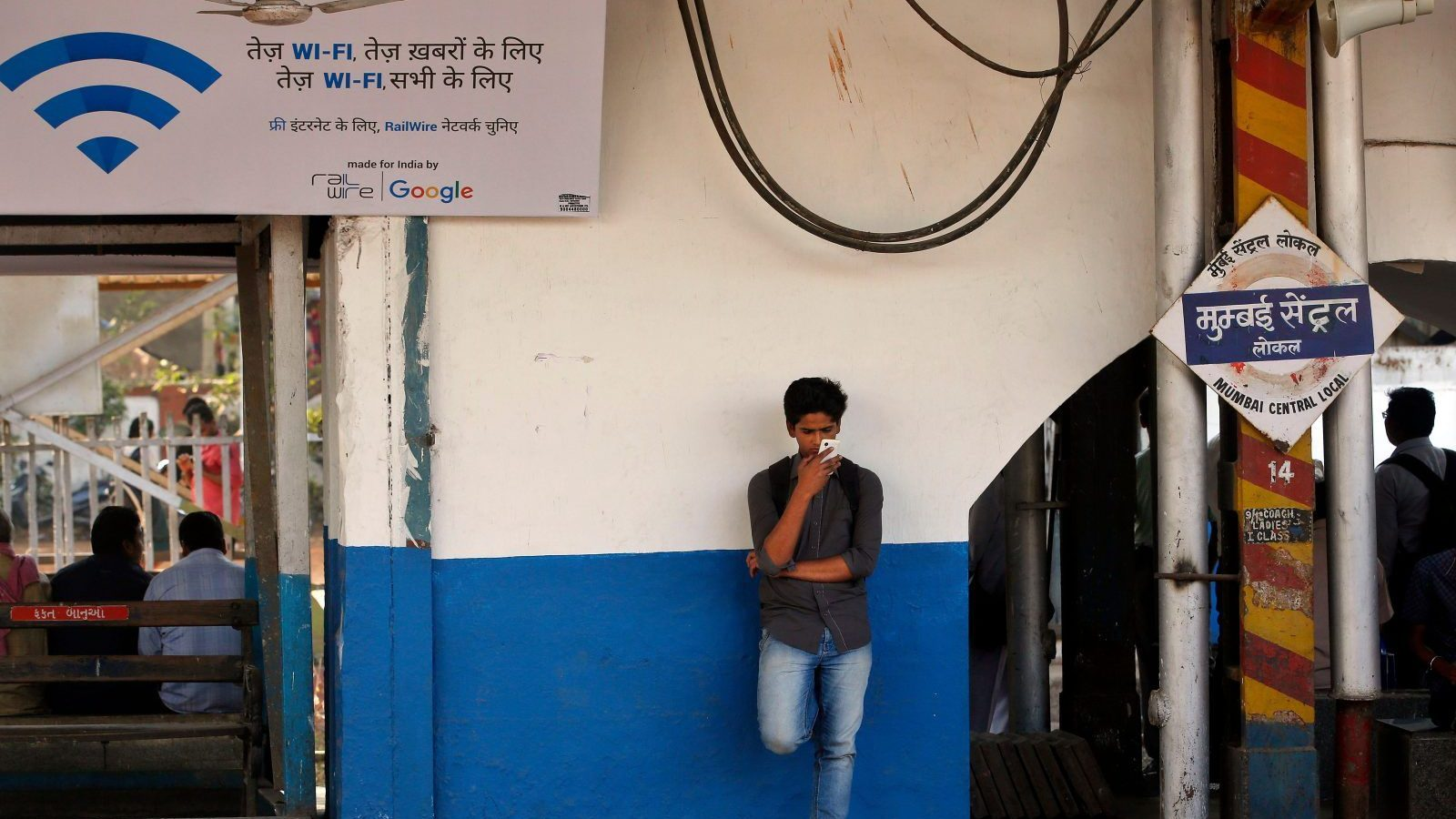 An Indian traveler uses a free WiFi service to browse the net at Mumbai Central Train Station in Mumbai, India, Friday, Jan. 22, 2016. Google Inc. has begun offering free WiFi to Mumbai train passengers in hopes of boosting its role in the Indian market. A poster on the left says 'fast WiFi, for fast news, fast WiFi, for everyone'. (AP Photo/Rajanish Kakade)