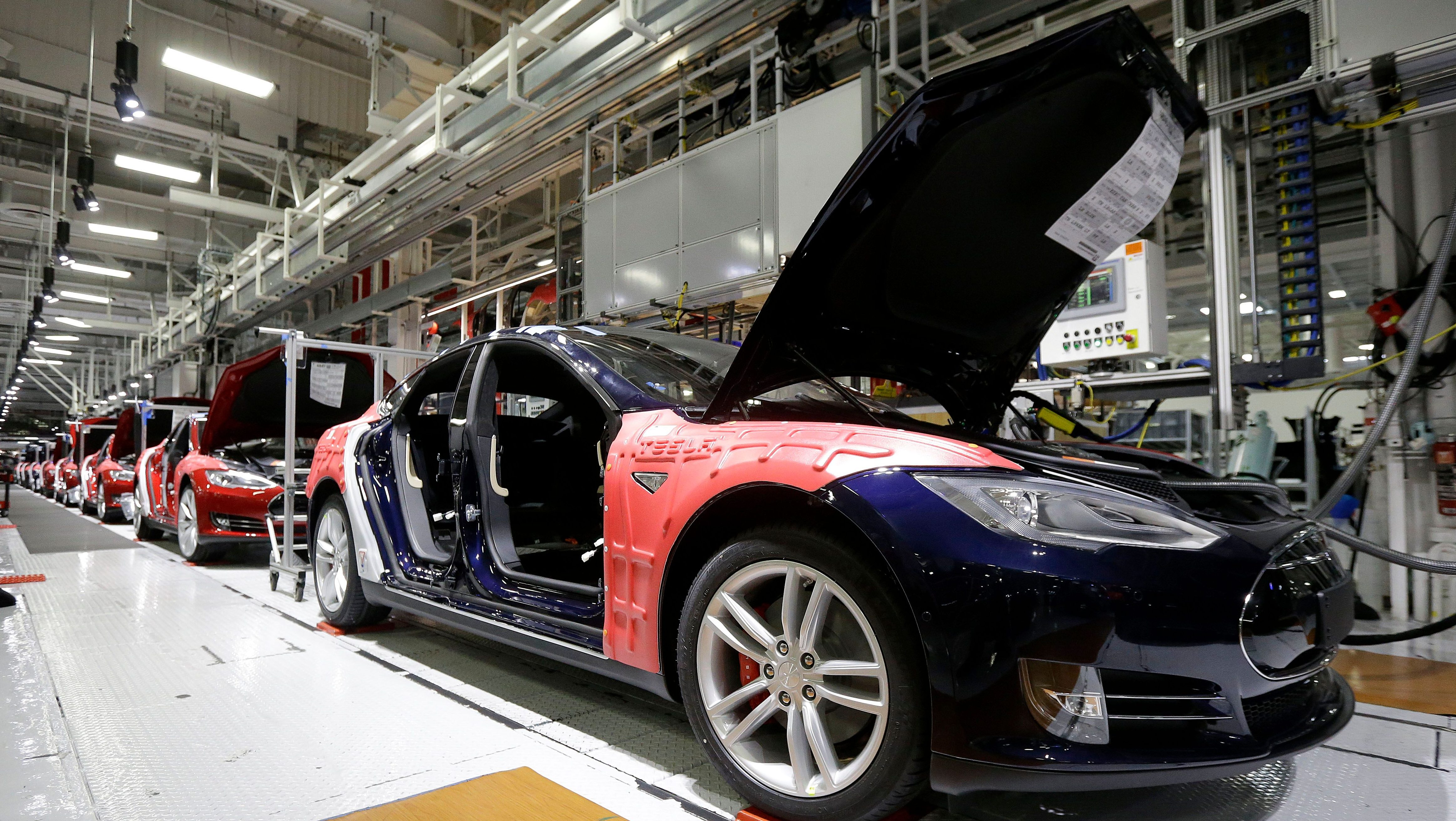 FILE - In this May 14, 2015, file photo, Tesla Model S cars are shown in the Tesla factory in Fremont, Calif. Tesla's second-quarter deliveries surged 52 percent to set a company record exceeding 11,000 vehicles, the electric car maker said Thursday, July 2, 2015. (AP Photo/Jeff Chiu, File)