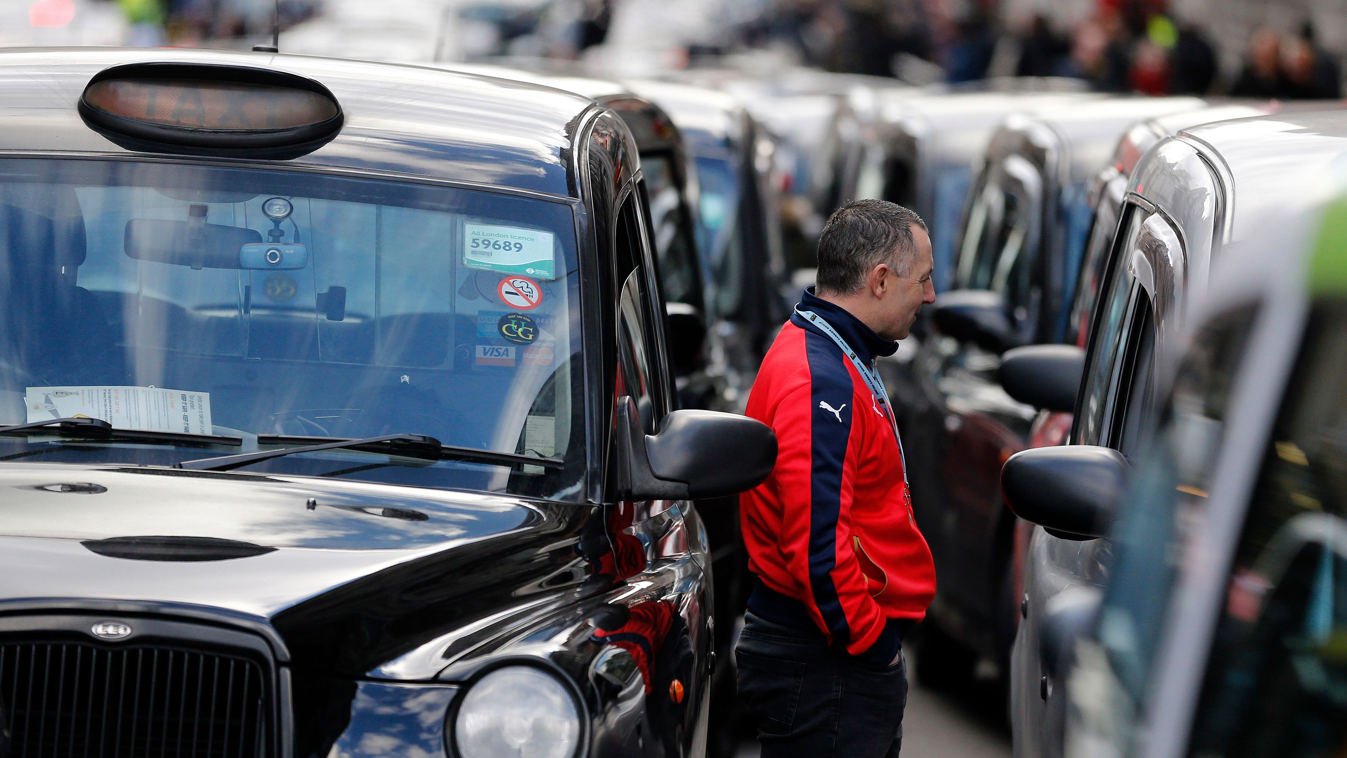 London taxis block the roads in central London, Wednesday, Feb. 10, 2016. Drivers are concerned with unfair competition from services such as Uber. (AP Photo/Frank Augstein)