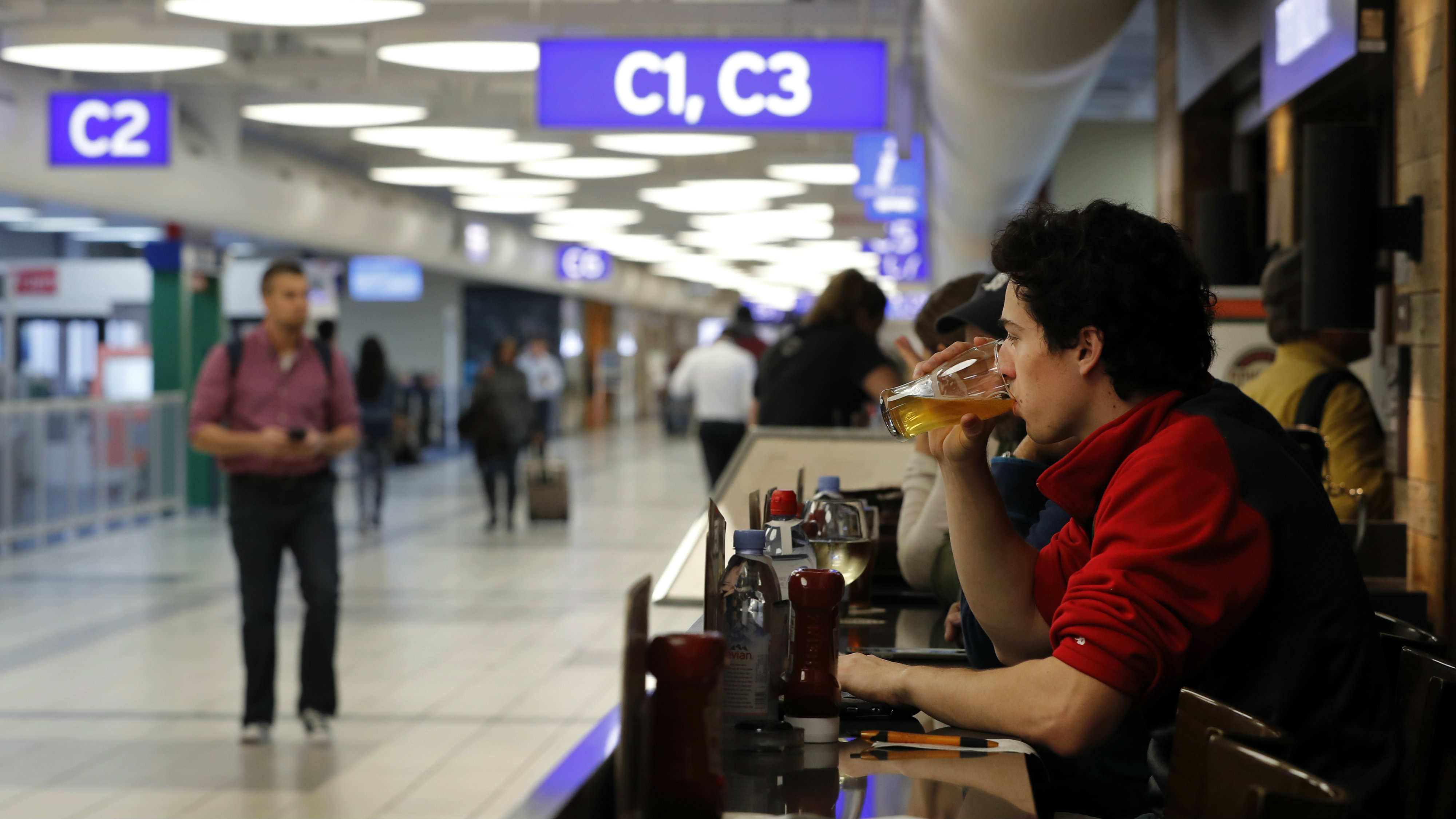 Man drinking a pint in an airport