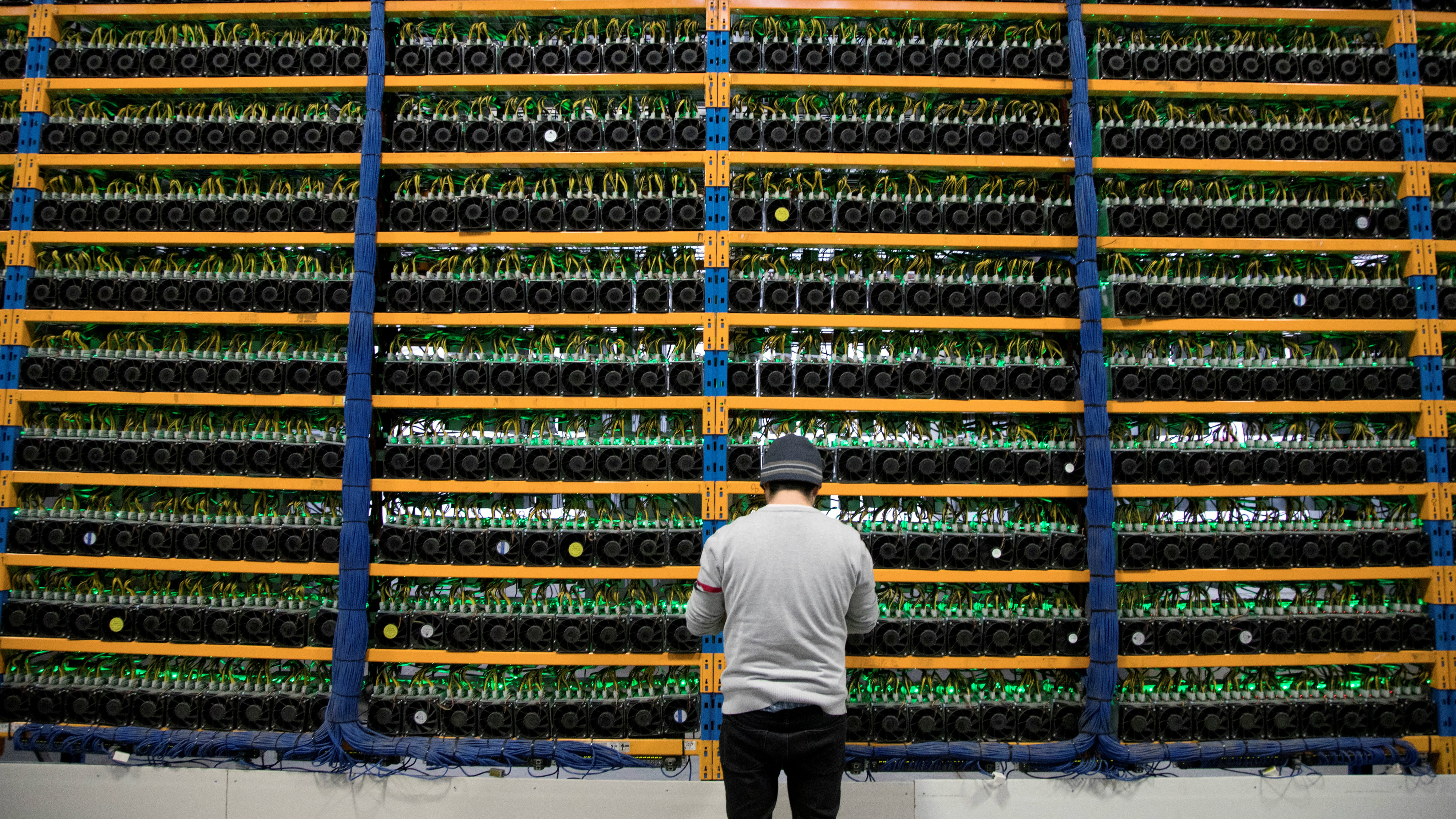 A worker checks the fans on miners, at the cryptocurrency farming operation, Bitfarms, in Farnham, Quebec, Canada, February 2, 2018.