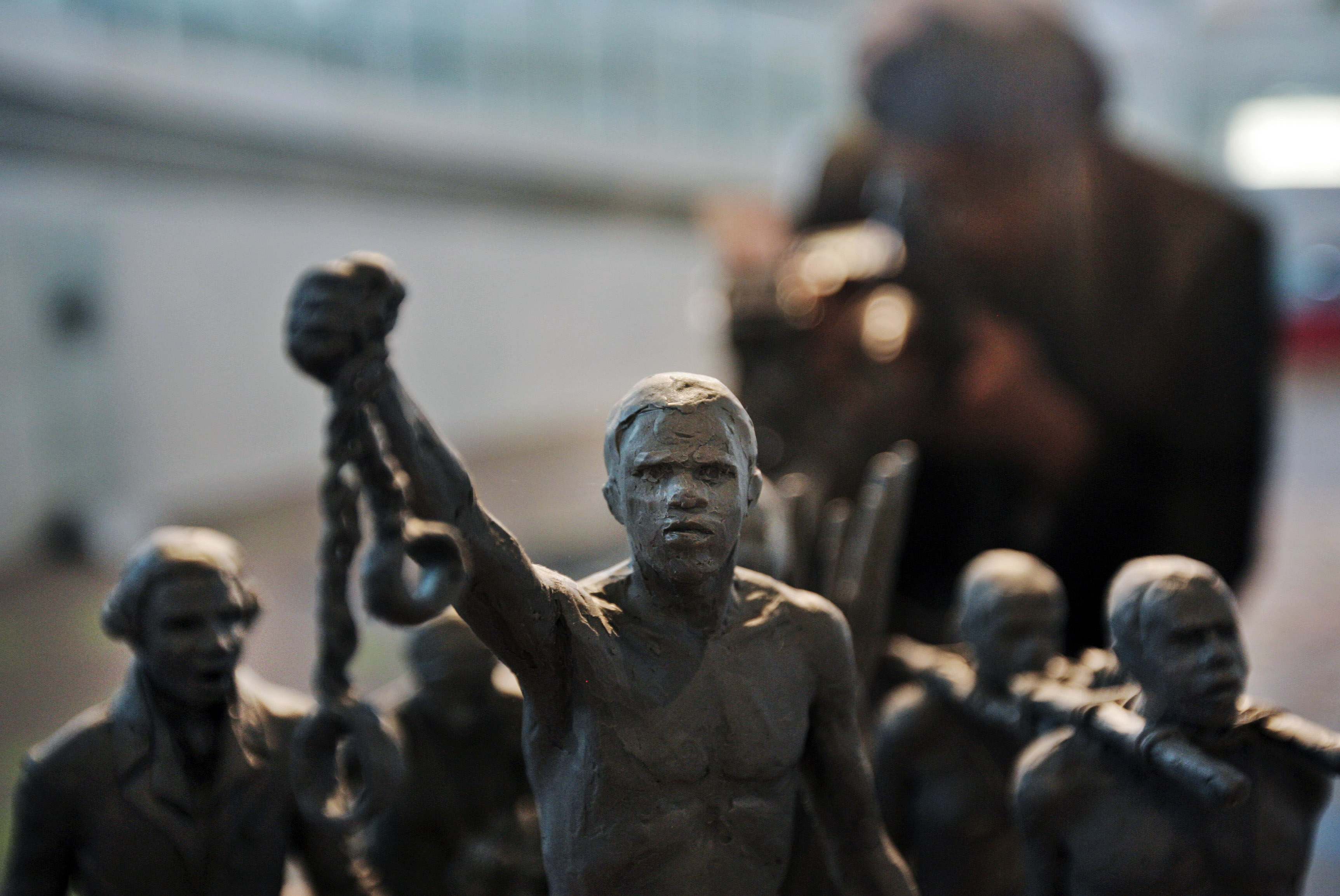 A man photographs a maquette of a statue, at City Hall, London, Monday, Aug.18, 2008. Mayor of London Boris Johnson, attended the presentation of the maquette of a statue, which will stand as a permanent slavery memorial statue.