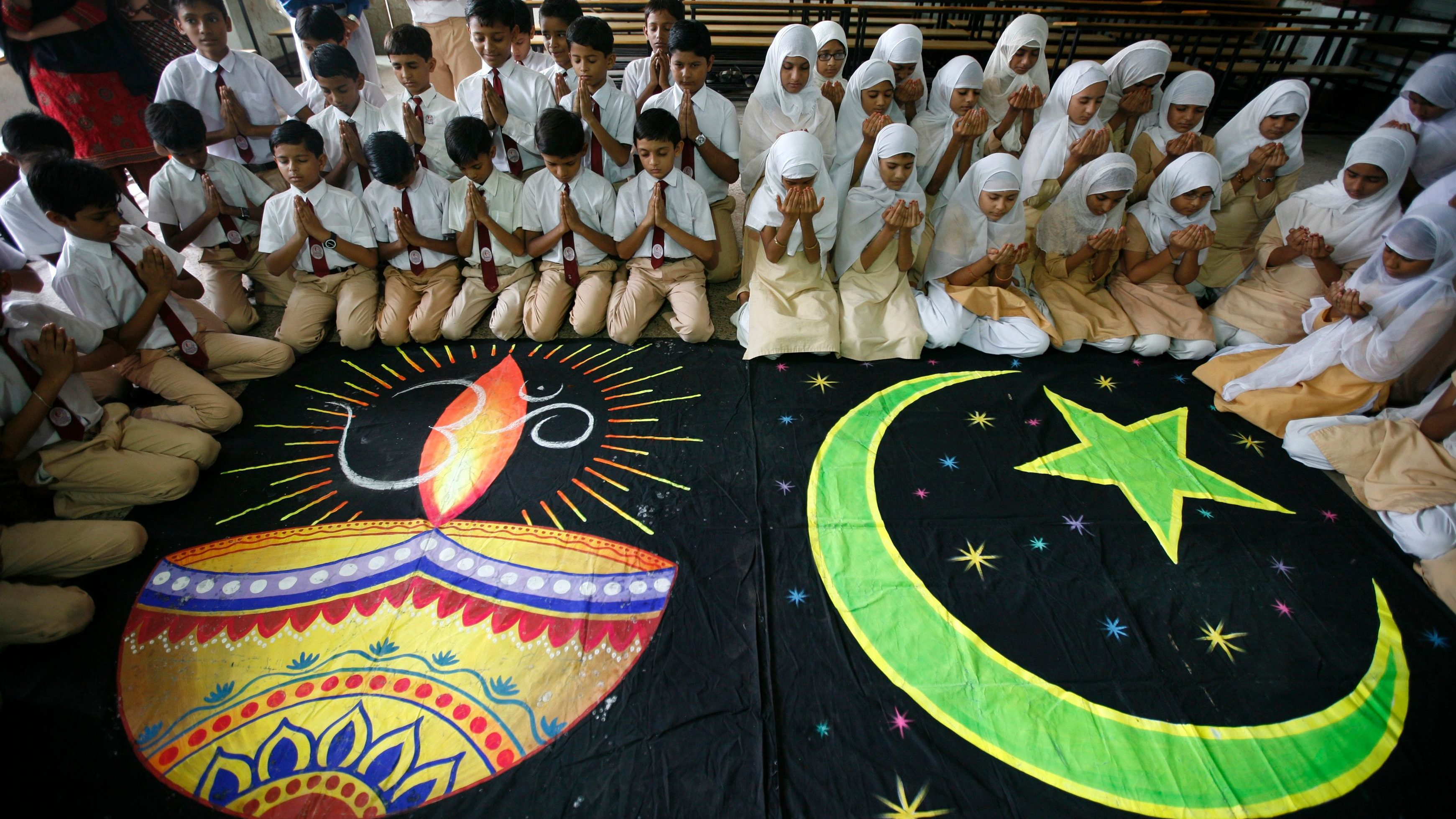 Hindu and Muslim school children offer prayers for peace inside their school in Ahmedabad on September 23, 2010.