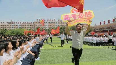 "Teachers run with signs as they cheer for students at a rally ahead of the annual national college entrance examination, or ""gaokao"", at a high school in Hengshui, Hebei province, China May 24, 2018."