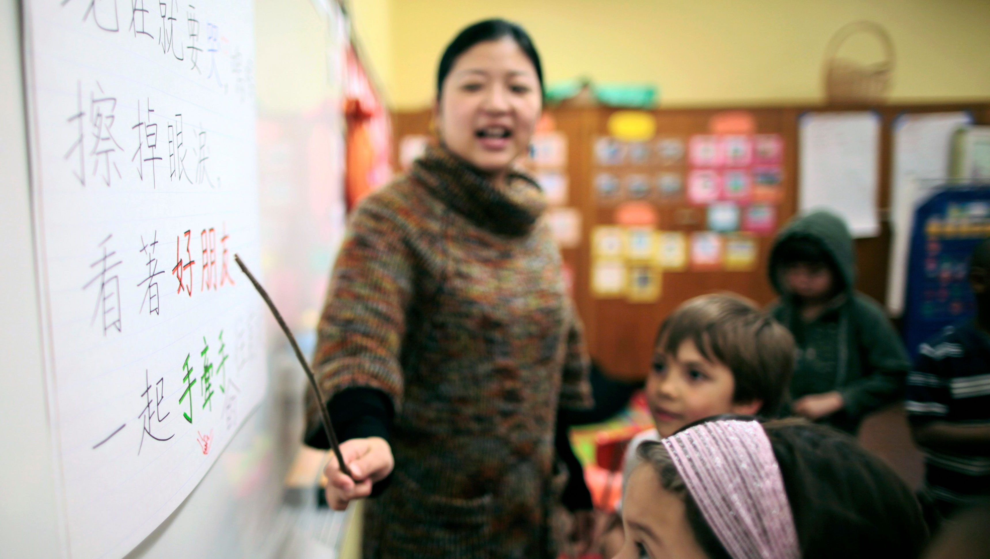 Teacher Kennis Wong (L) points to Chinese characters on the board at Broadway Elementary School in Venice, Los Angeles, California, April 11, 2011. The school launched one of only two English-Mandarin Chinese dual-language immersion programs in the Los Angeles Unified School District in September 2010.
