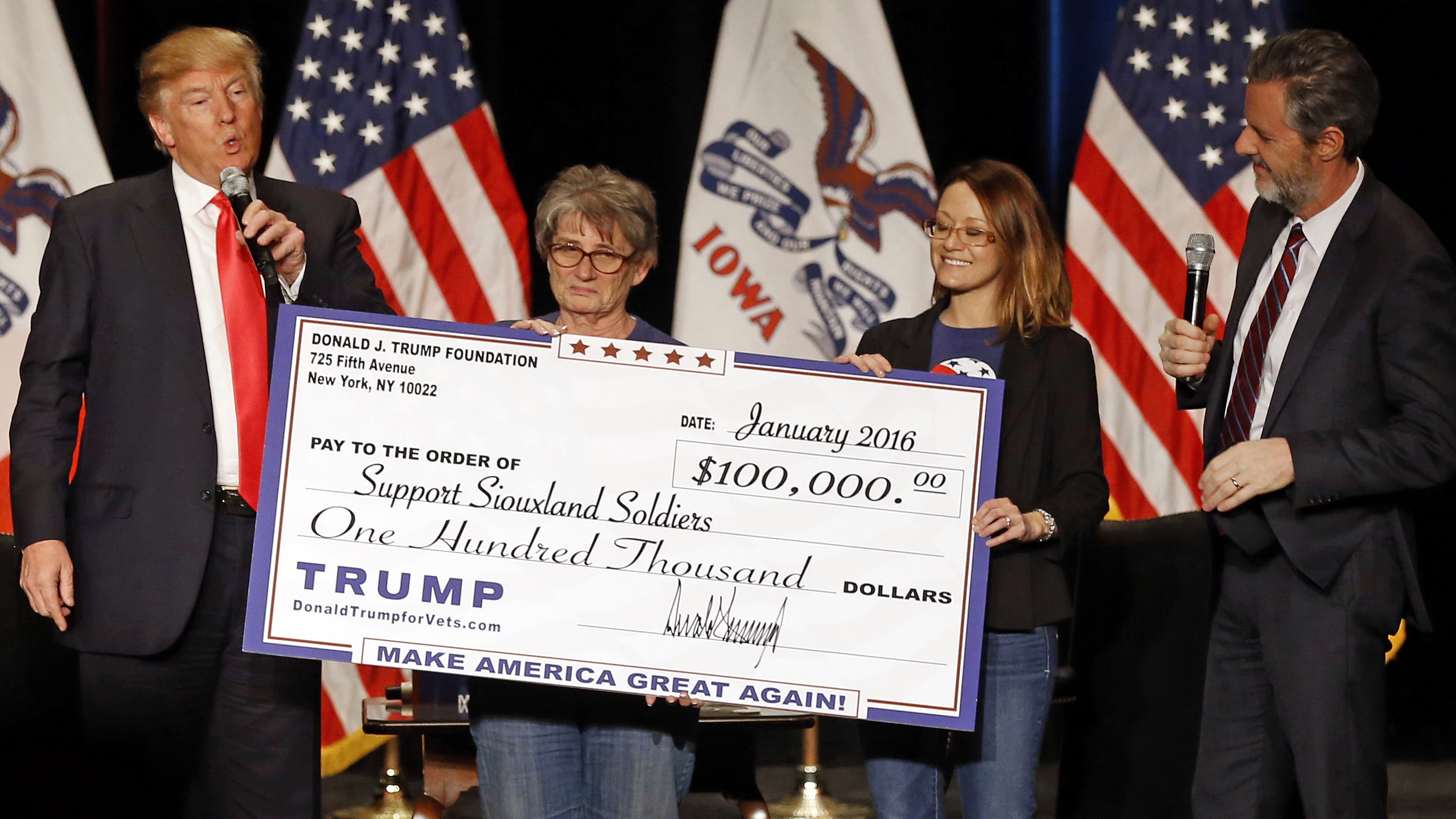 FILE - In this Jan. 31, 2016 file photo, Republican presidential candidate Donald Trump, left, presents a check to members of Support Siouxland Soldiers during a campaign event at the Orpheum Theatre in Sioux City, Iowa. Under pressure to account for money he claimed to raise for veterans, an angry and irritated Donald Trump listed charities Tuesday, May 31, 2016, he says have now received millions of dollars from a fundraiser he held in January. Also pictured is Jerry Falwell, Jr., right, president of Liberty University