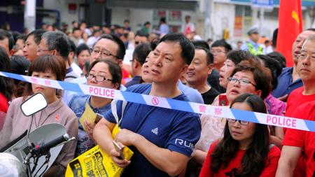 "Parents wait behind police cordon outside the venue for the annual national college entrance examination, or ""gaokao"", in Shenyang, Liaoning province, China June 7, 2018."