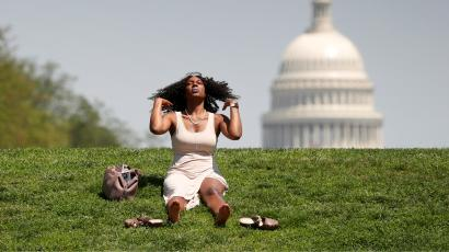 Woman sits on grass in heat