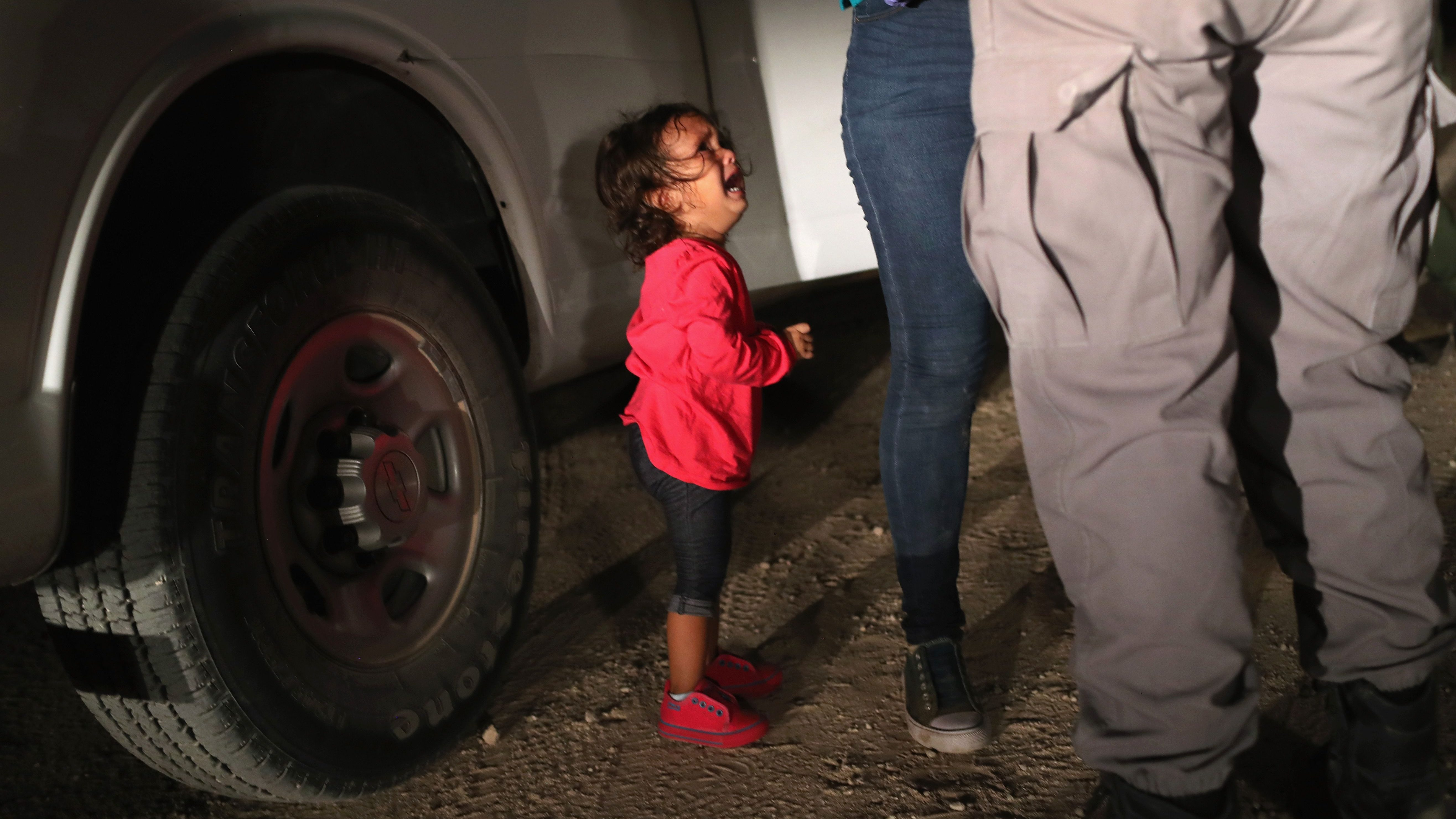 """MCALLEN, TX - JUNE 12: A two-year-old Honduran asylum seeker cries as her mother is searched and detained near the U.S.-Mexico border on June 12, 2018 in McAllen, Texas. The asylum seekers had rafted across the Rio Grande from Mexico and were detained by U.S. Border Patrol agents before being sent to a processing center for possible separation. Customs and Border Protection (CBP) is executing the Trump administration's """"zero tolerance"""" policy towards undocumented immigrants. US Attorney General Jeff Sessions also said that domestic and gang violence in immigrants' country of origin would no longer qualify them for political asylum status."""