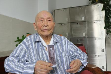 Luo Danhong holding a picture of him wearing the People's Volunteer Army uniform during the Korean war.