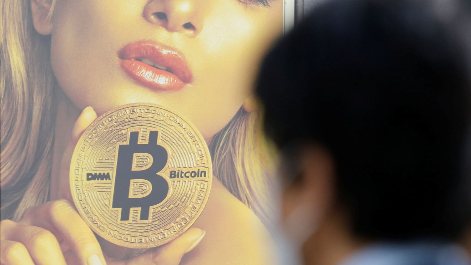 A man stands near an advertisement of a cryptocurrency exchange in Tokyo, Japan March 30, 2018. Picture taken March 30, 2018