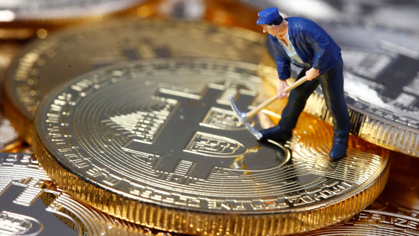 A small toy figure is seen on representations of the Bitcoin virtual currency in this illustration picture, December 26, 2017.