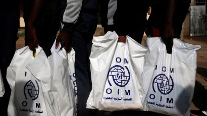 Gambian migrants deported from Libya stand in line with plastic bags from the International Organization for Migration