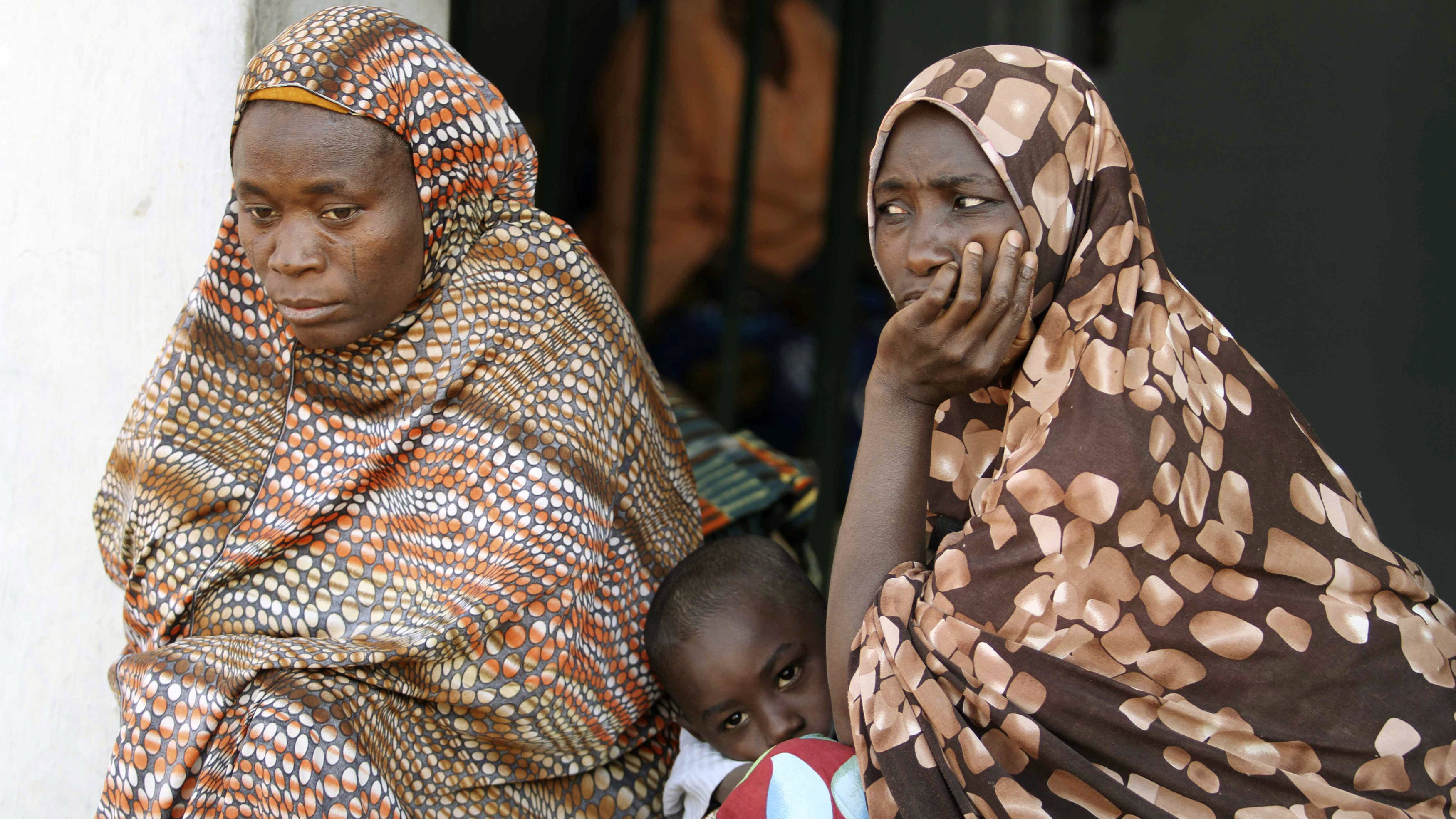 Women sit with their children at a camp for internally displaced people in Nigeria's central city of Jos December 26, 2010. Clashes broke out between armed Christian and Muslim groups near the central Nigerian city of Jos on Sunday, a Reuters witness said, after Christmas Eve bombings in the region killed more than 30 people.