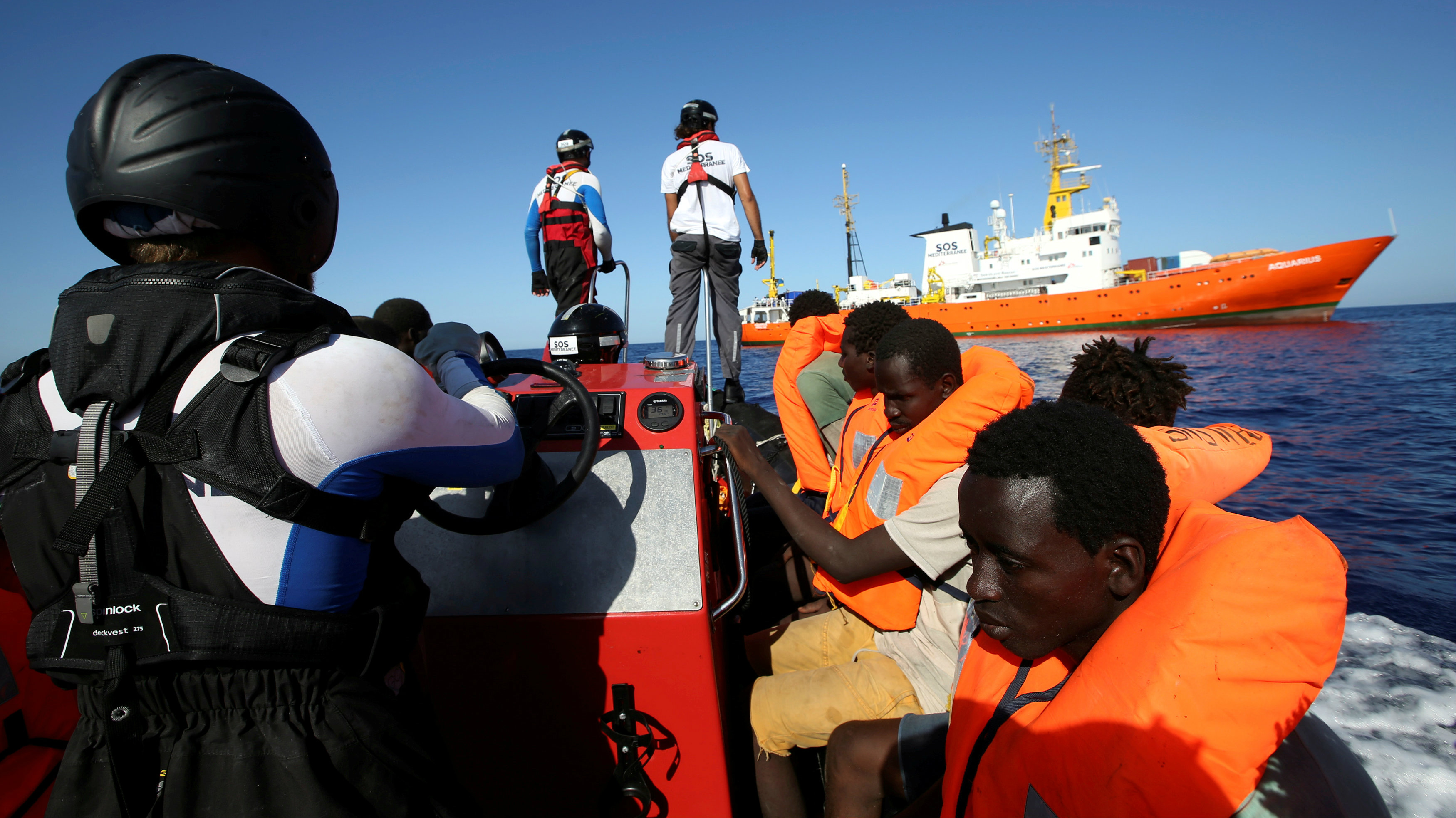 Migrants on a rubber boat are rescued by the SOS Mediterranee organisation during a search and rescue (SAR) operation with the MV Aquarius rescue ship (background) in the Mediterranean Sea, off the Libyan Coast, September 14, 2017.