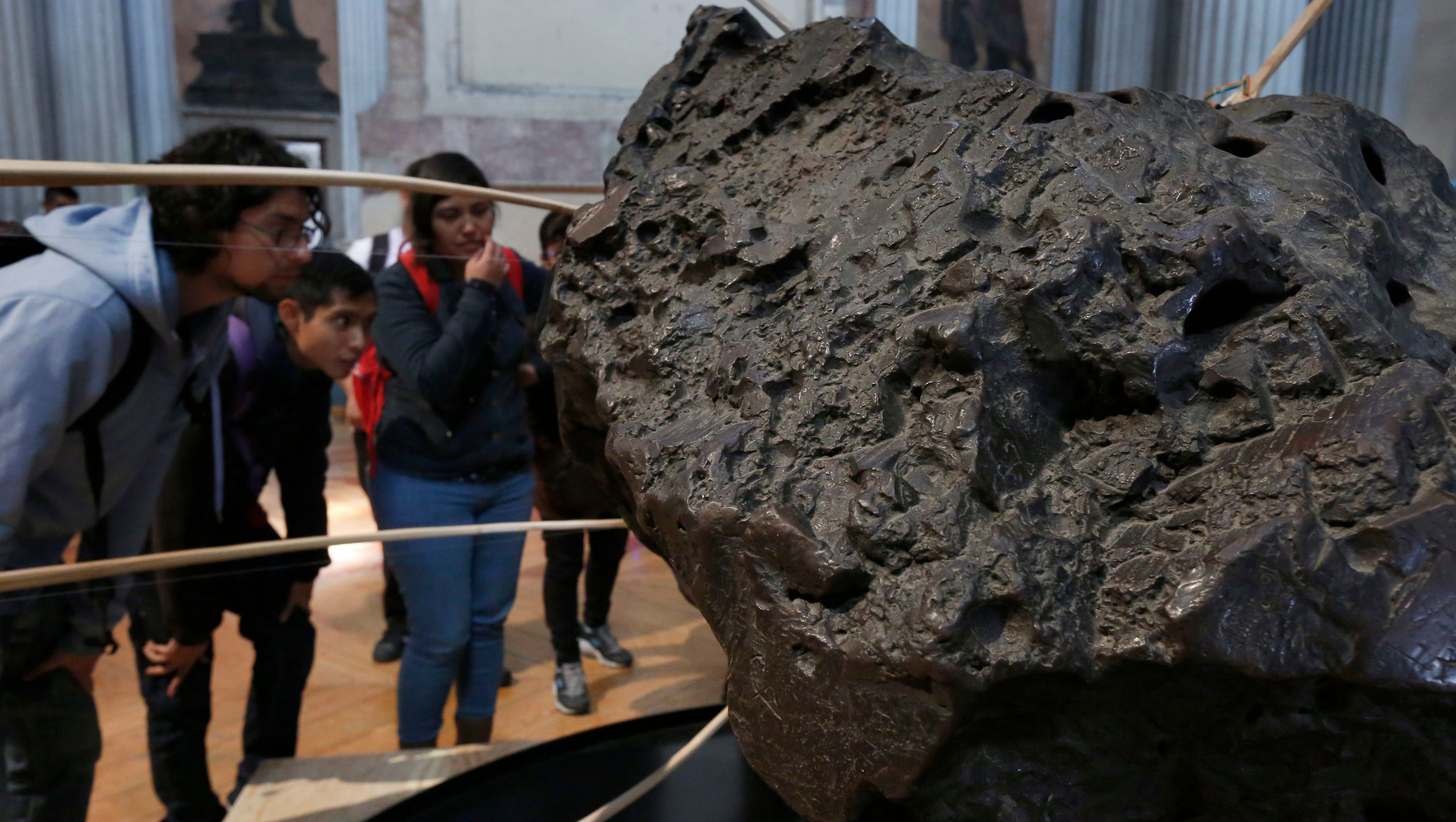 """People look at """"La Concepcion"""" meteorite at the Ex Teresa Arte Actual Museum in Mexico City, Monday, Oct. 10, 2016. The Meteorite was found in the state of Chihuahua during the XVII century and is being displayed with special instruments that create sounds based on the meteorite's surface irregularities and magnetic field. (AP Photo/Marco Ugarte)"""