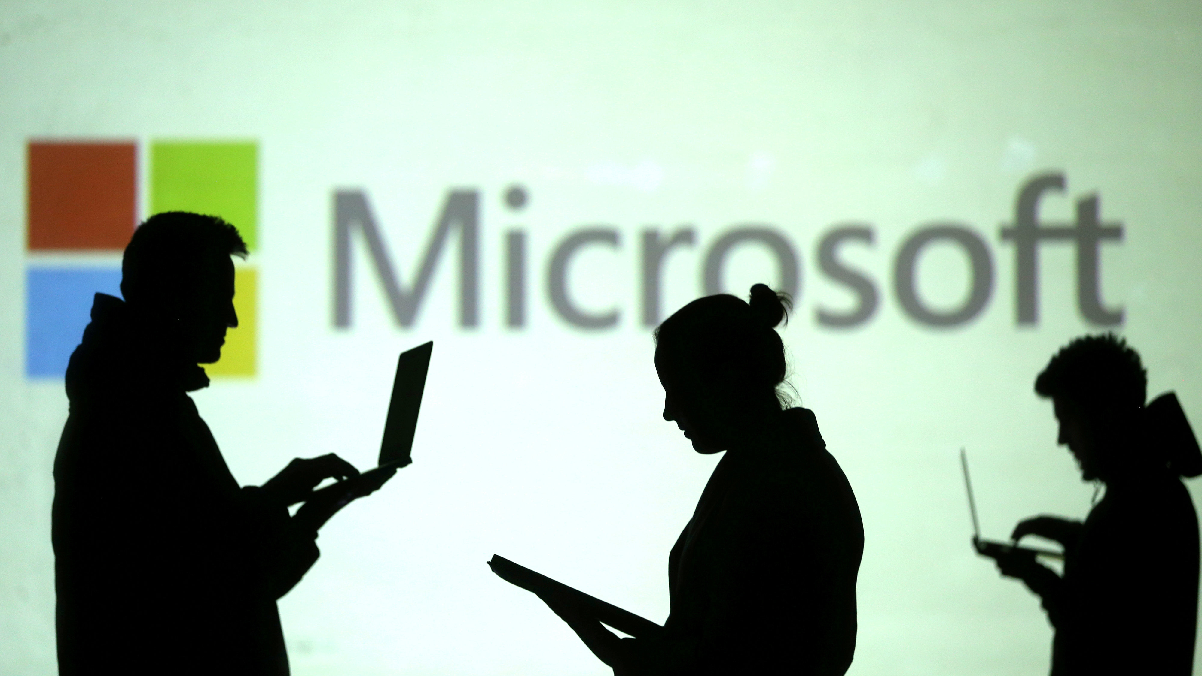 Silhouettes of laptop users are seen next to a screen projection of Microsoft logo in this picture illustration taken March 28, 2018.
