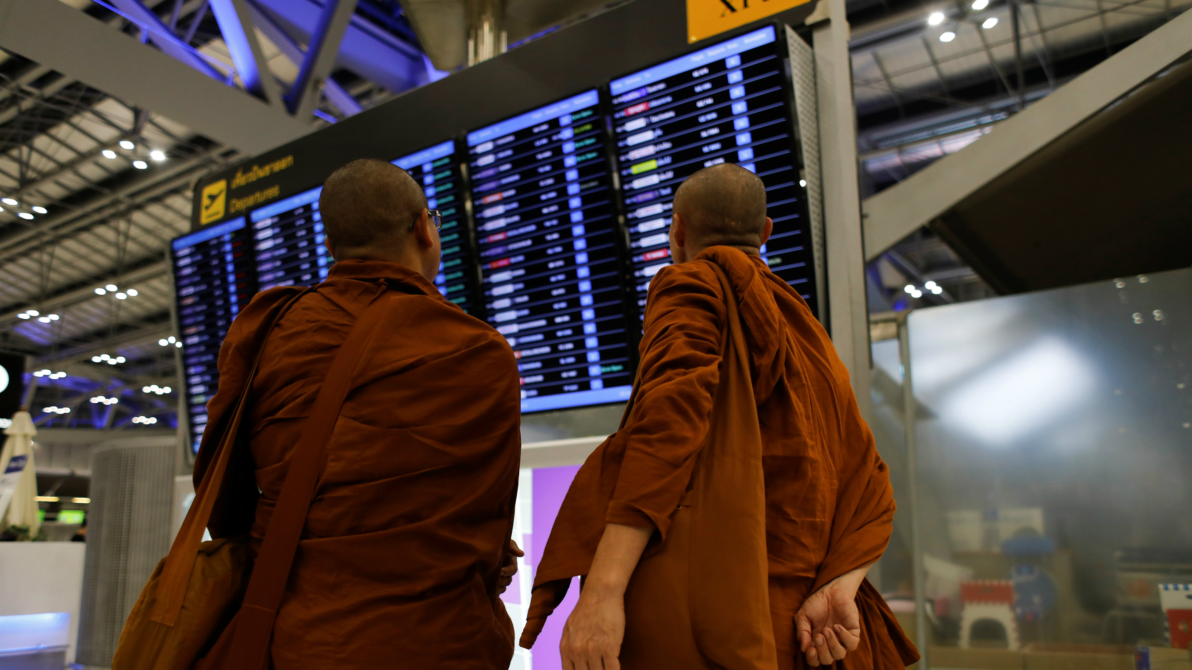 Monks look at airport departure board