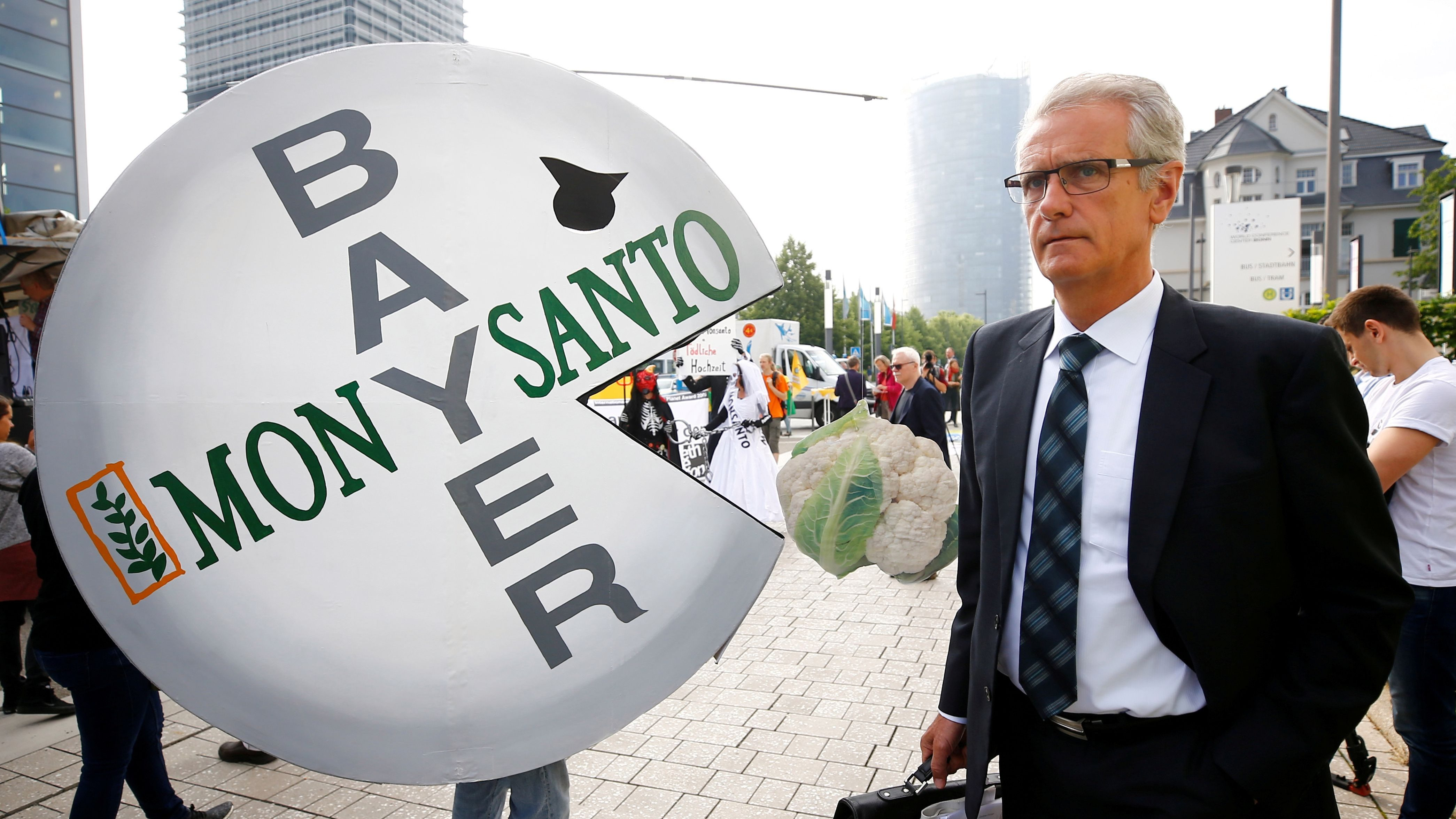 Protester holding a sign at the Bayer shareholder meeting in Bonn, Germany, protesting the purchase of Monsanto.