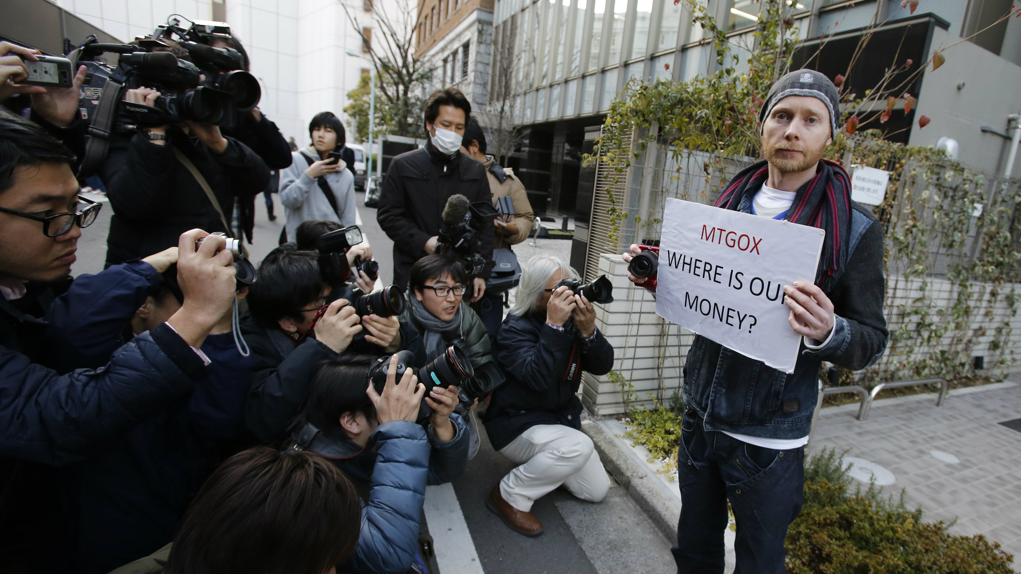 Kolin Burges (R), a self-styled cryptocurrency trader and former software engineer from London, holds a placard to protest against Mt. Gox, as photographers take photos of him in front of the building where the digital marketplace operator was formerly housed in Tokyo February 26, 2014. Japanese authorities are looking into the abrupt closure of Mt. Gox, the top government spokesman said on Wednesday in Tokyo's first official reaction to the turmoil at what was the world's biggest exchange for bitcoin virtual currency.