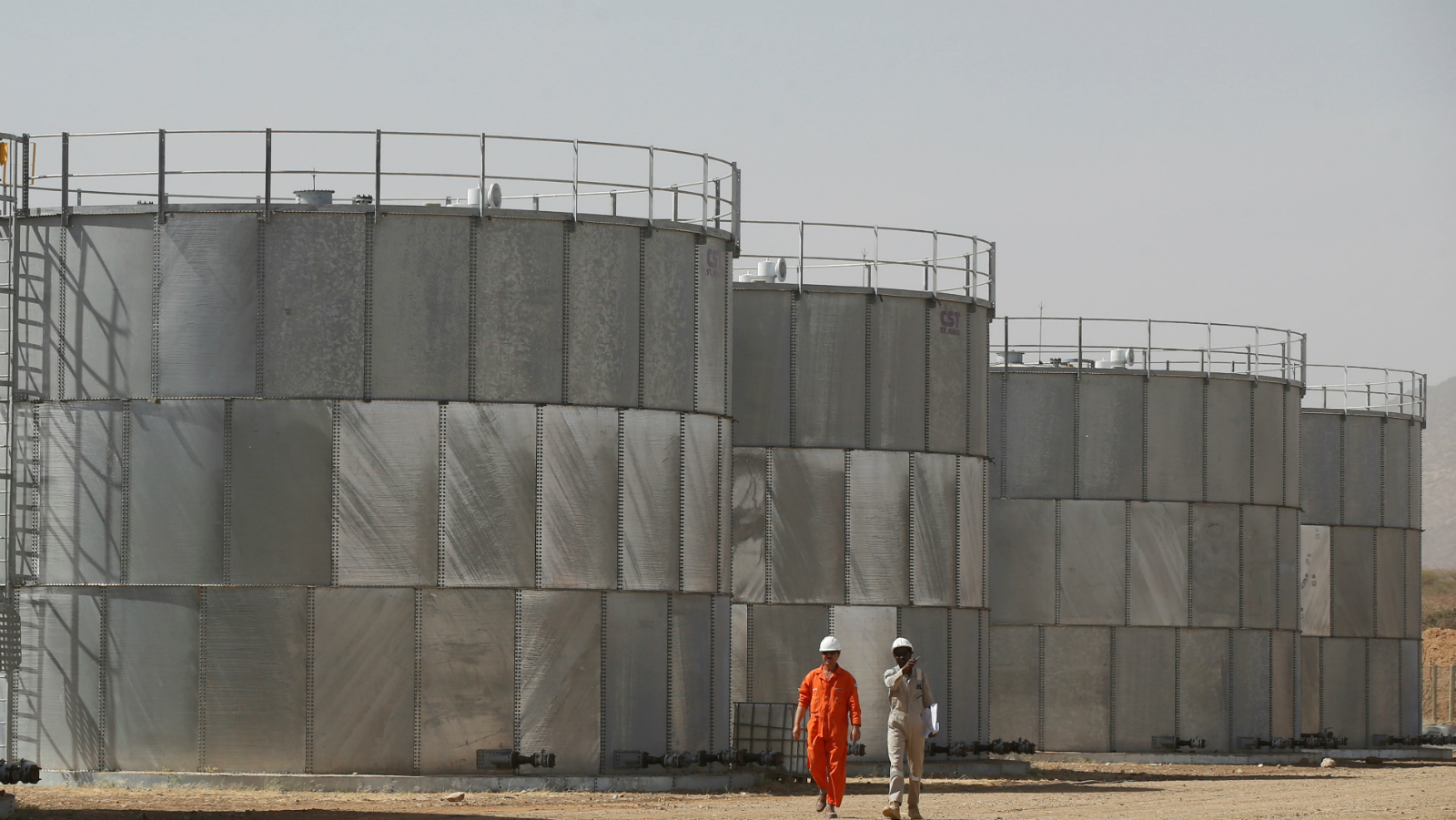 Workers walk past storage tanks at Tullow Oil's Ngamia 8 drilling site in Lokichar, Turkana County, Kenya, February 8, 2018. Picture taken February 8, 2018.
